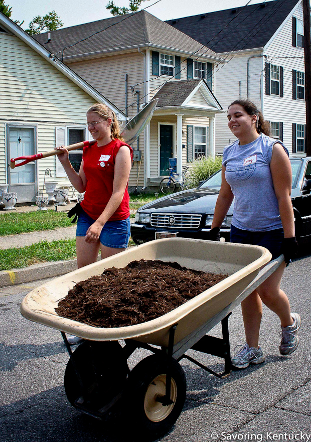 Student volunteers from the University of Kentucky move finished compost to nurture a garden