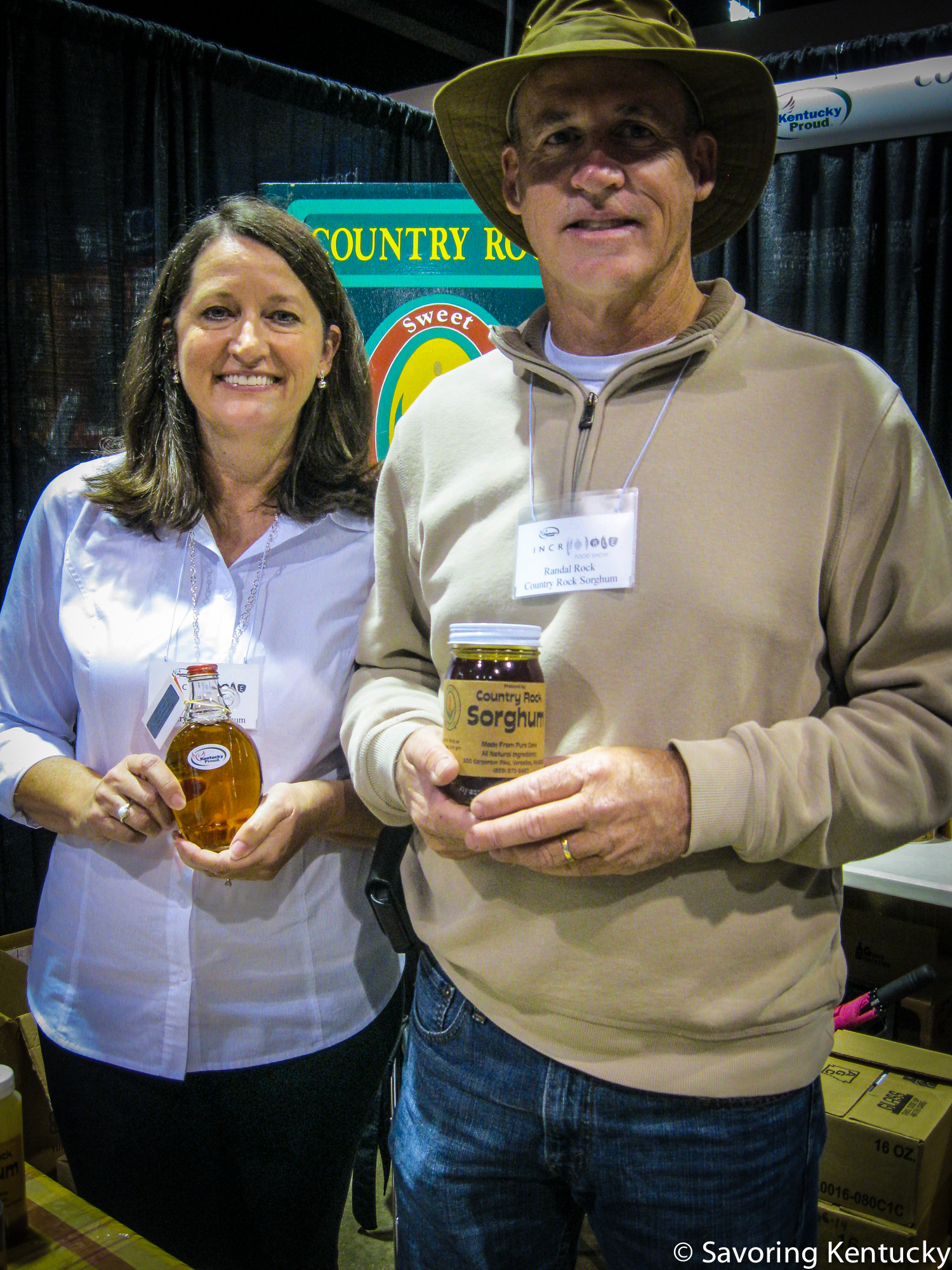 Jill Rock and Randal Rock, part of the Country Rock Sorghum enterprise. Jill holds maple syrup and Randal holds sorghum, both vintage 2014.