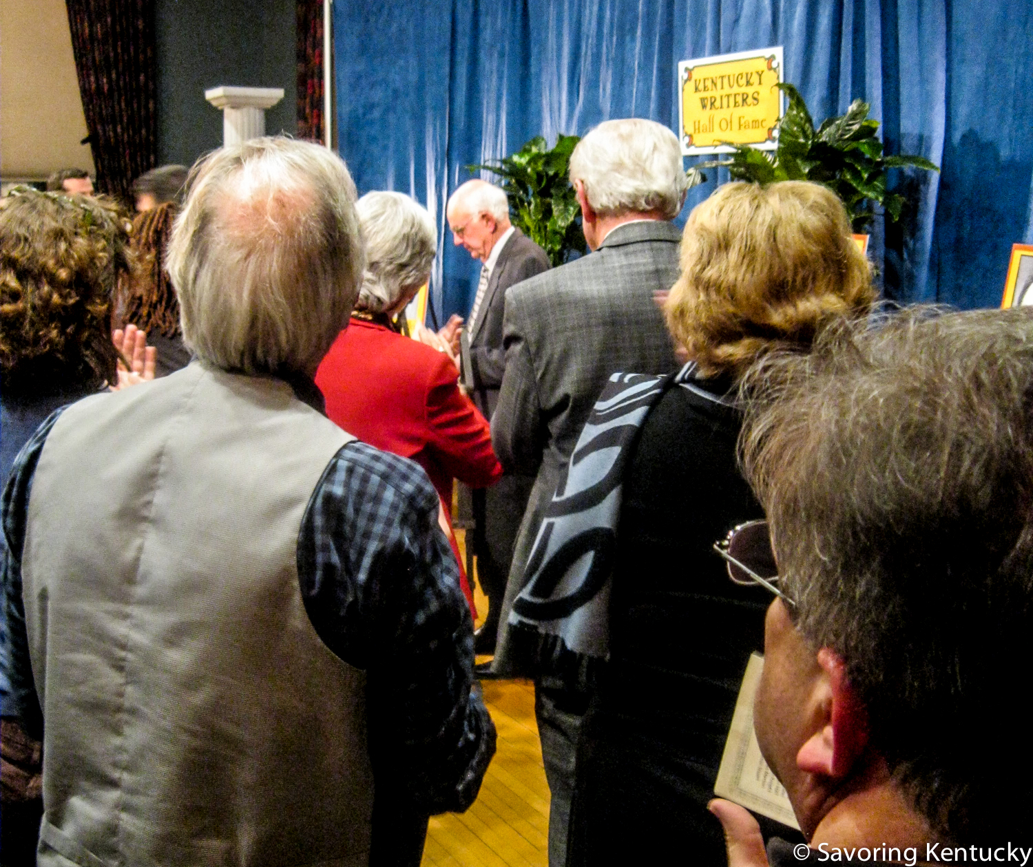 Wendell Berry at center. From back left, photographer and artist Guy Mendes in vest, Kentucky Lieutenant Governor Crit Luallen in red. From back right, Kentucky Monthly editor and publisher Steve Vest, Kentucky Arts Council director Lori Meadows, Lynn Luallen.
