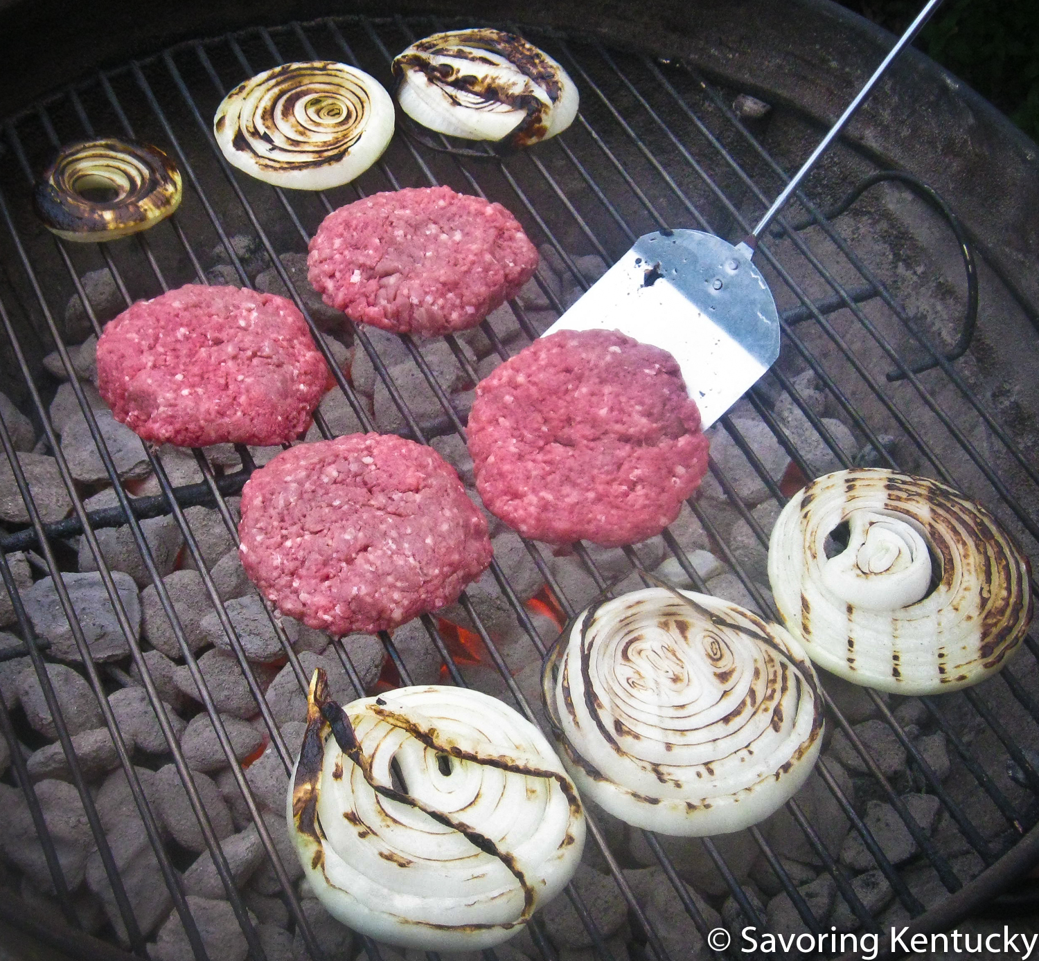 Elmwood Stock Farm  certified organic, pastured ground round burgers keep warm company with some Kentucky candy onion slices, preparing to grace a bun.