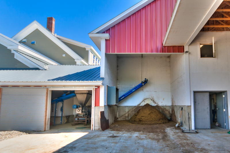 A conventional manure conveyor in the barn loads a hopper seen to the left.