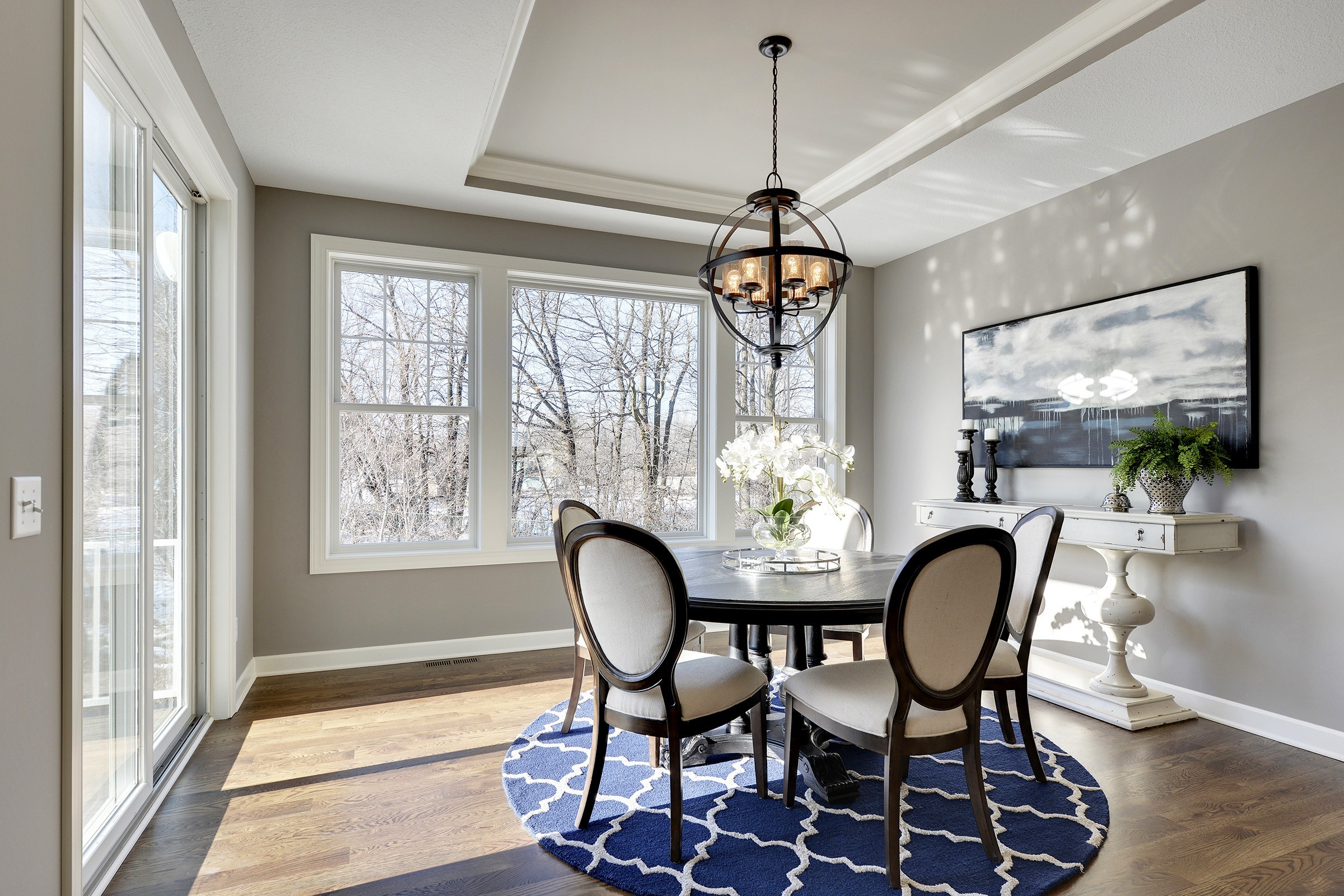 The white arrangement of flowers go well with the blue accent pieces in this dining room.