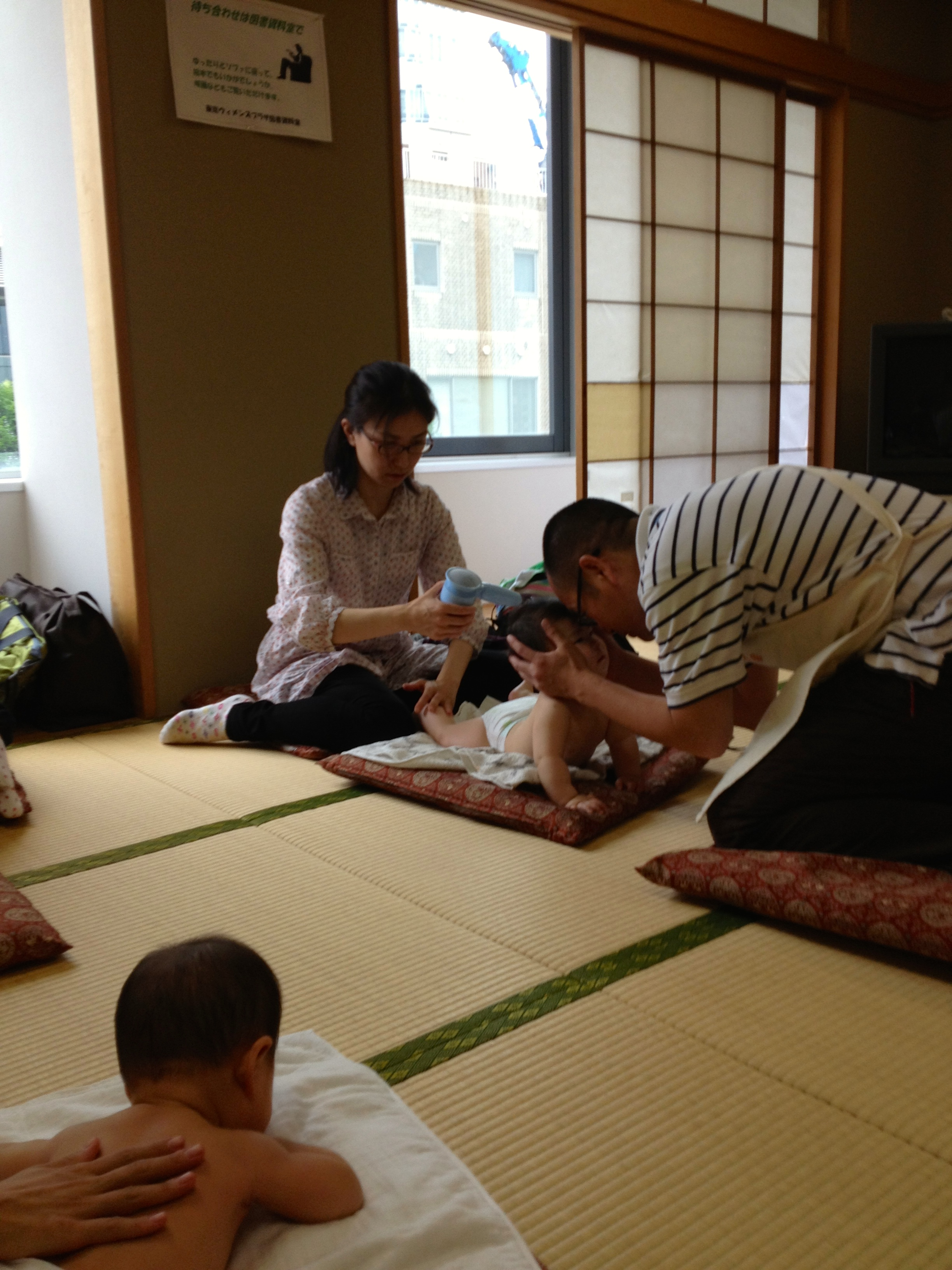 A parent trying the hairdryer technique (In lieu of moxa) while the acupuncturist teacher engages the baby