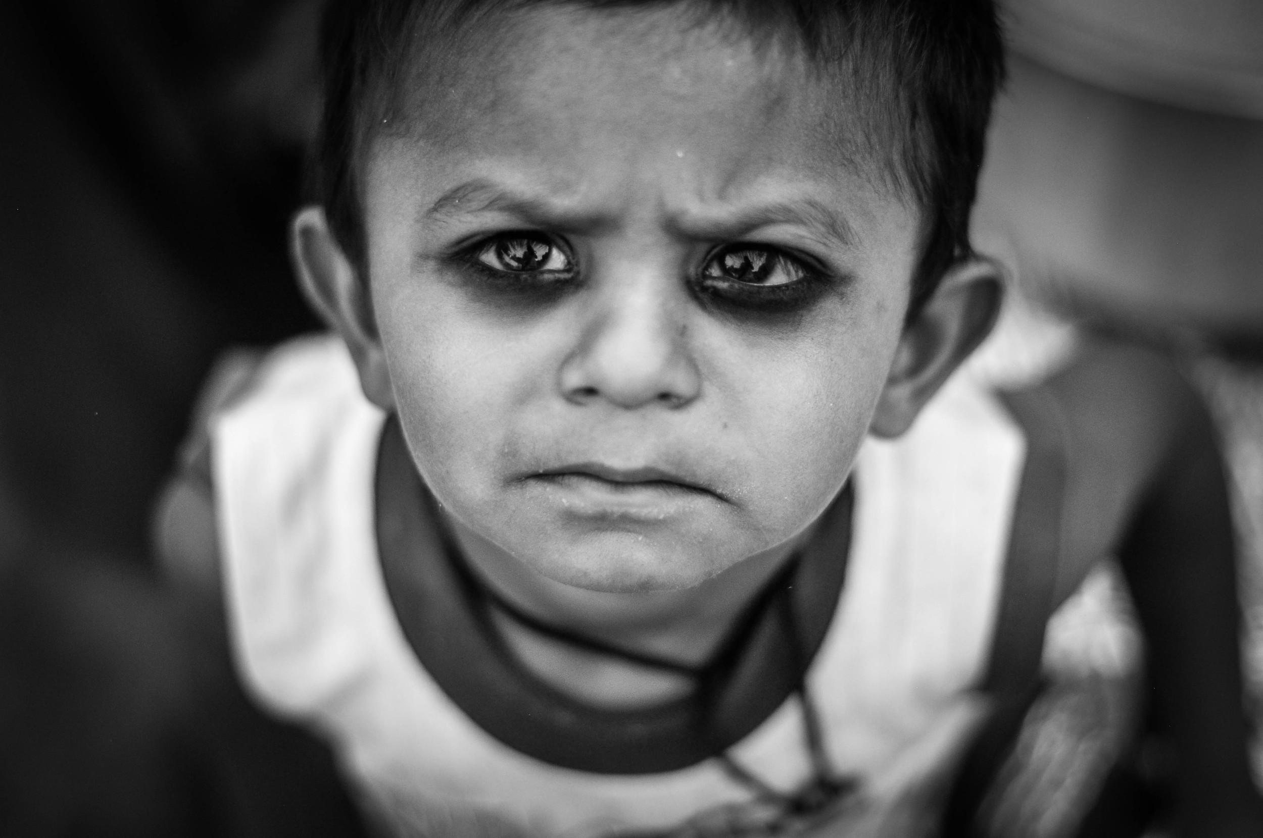 Hindu parents pain their children's eyes black because they believe it will keep away bad spirits. Jasola Slum, India.