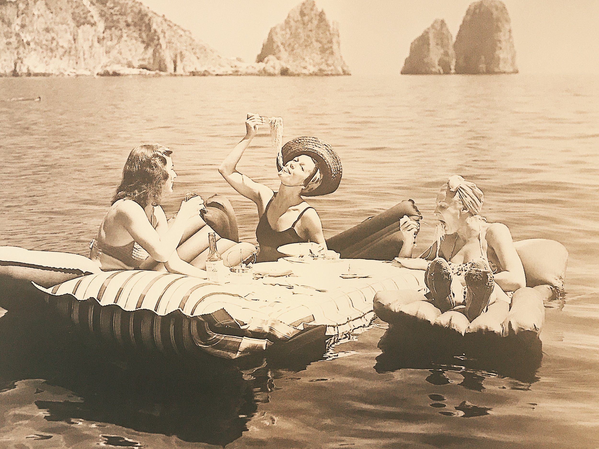 Photo of a photo. Hamilton Wright's 1939 capture of three young women eating spaghetti on raft.