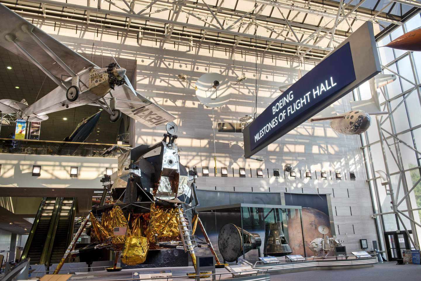 "The Apollo Lunar Module displayed as a centerpiece below the ""Spirit of St. Louis"" in the newly renovated Boeing Milestones of Flight Hall. / Image: Smithsonian Institution"