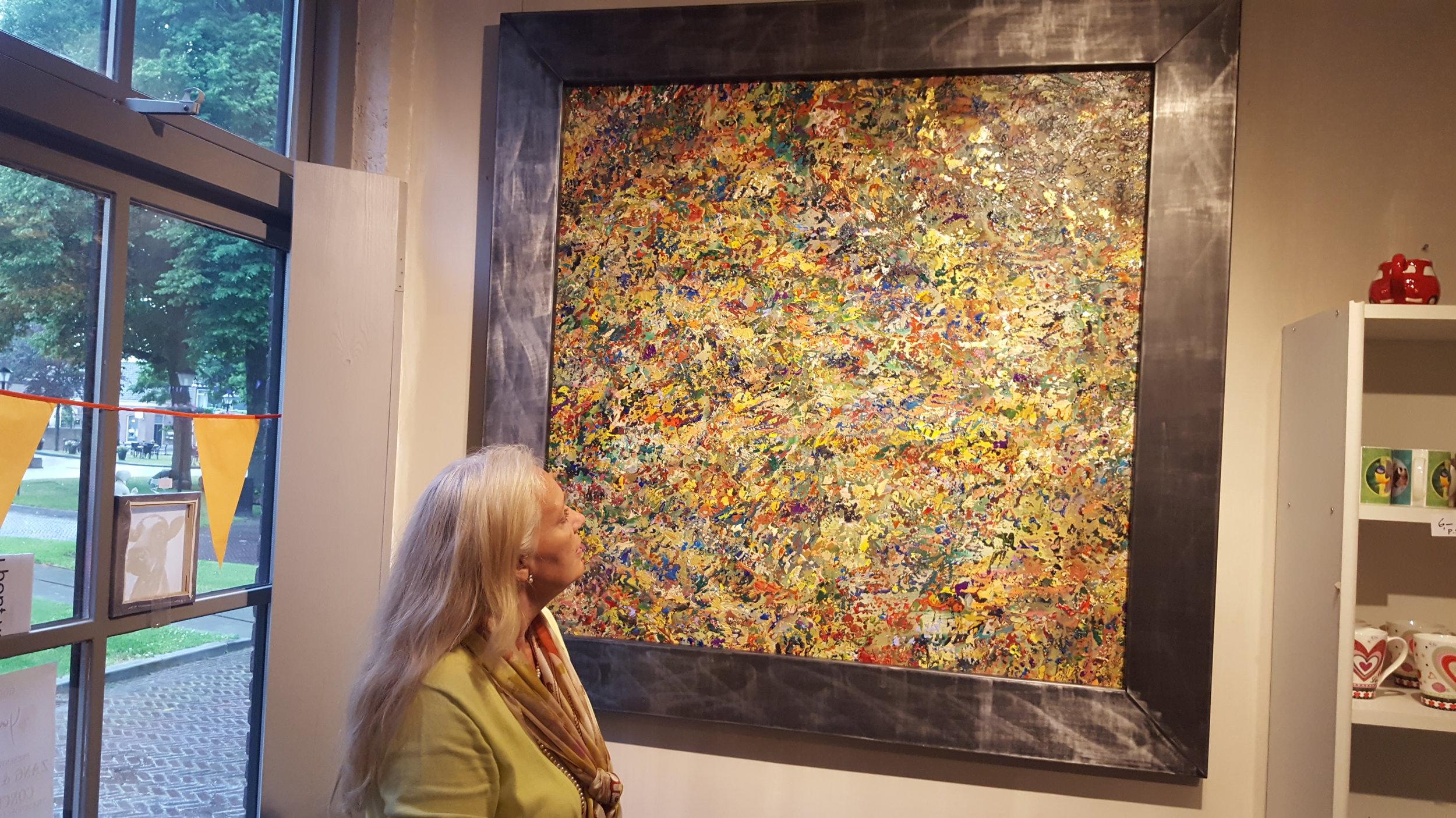 Femke Anne bij een van haar schilderijen, deze heeft een stalen lijst (die 15 kilo weegt)