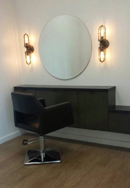 Custom Cabinet is finished with a black granite top and matte black hardware from  Details . Each drawer was custom fitted to accommodate the needs of a stylist. The round mirror softens the edgy finishes. Sconces are by Feiss and are available at  Lamps Plus .