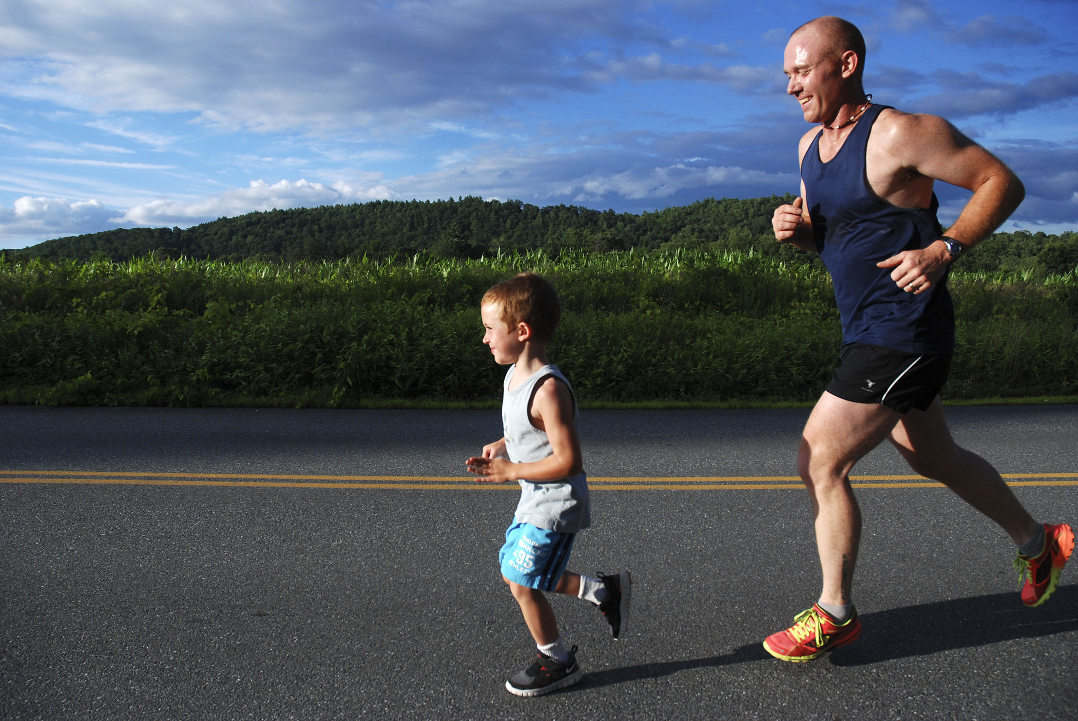Peyton Joslyn, 5, of Keene, runs with his father, Clint Joslyn, at the Red Clover Rovers fun run in Brattleboro, Vt. on July 25, 2013.