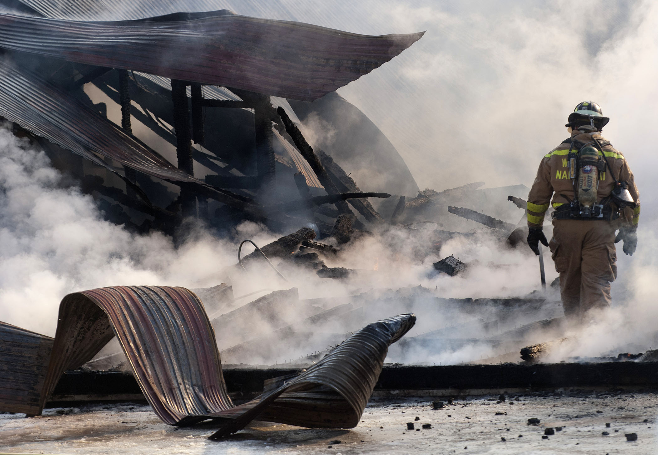 A firefighter walks through debris as firefighters work to keep flames under control at a barn fire on County Rd. in Walpole, N.H. on Friday, January 3rd.