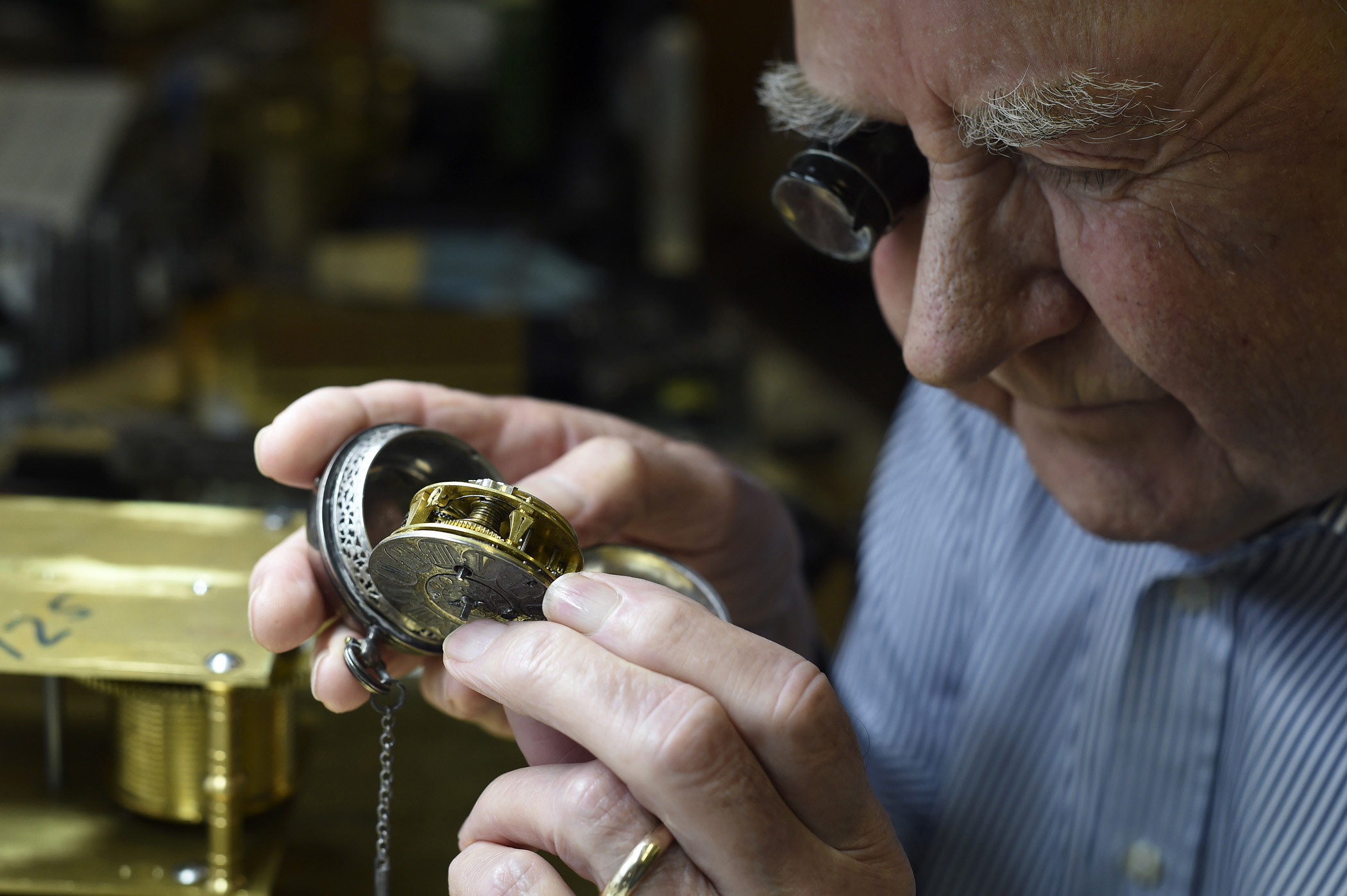 "Ray Bates, ""The British Clockmaker"" looks inside a watch at his workshop in Newfane, Vt. on September 10, 2014. Bates has been repairing and building clocks in his workshop for 50 years."