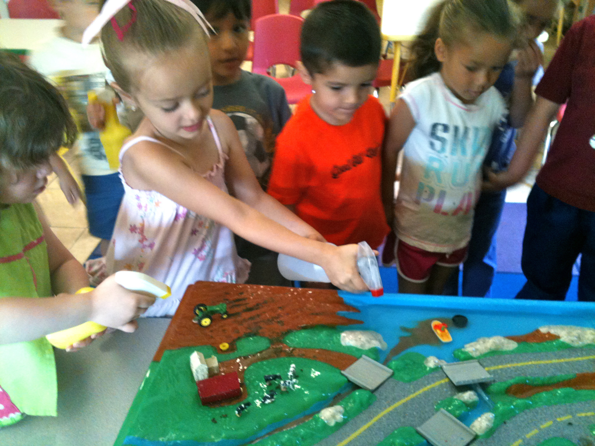 Students explore sources of water pollution using an Enviroscape watershed model during a class visit.