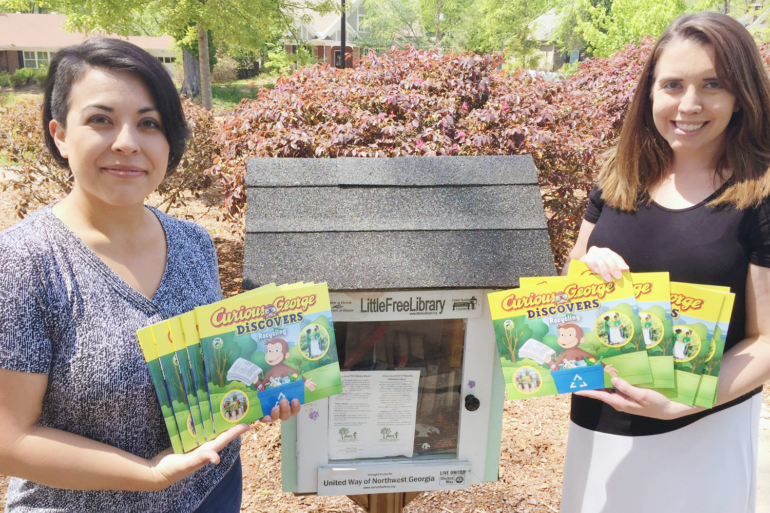 "Liz Swafford and Jessica Trivino display several copies of the book ""Curious George Discovers Recycling"" in front of a Free Little Library box. The Dalton-Whitfield Solid Waste Authority's Recycling Center donated 24 books to the Little Free Library Program hosted by the United Way of Northwest Georgia in honor of Earth Day."