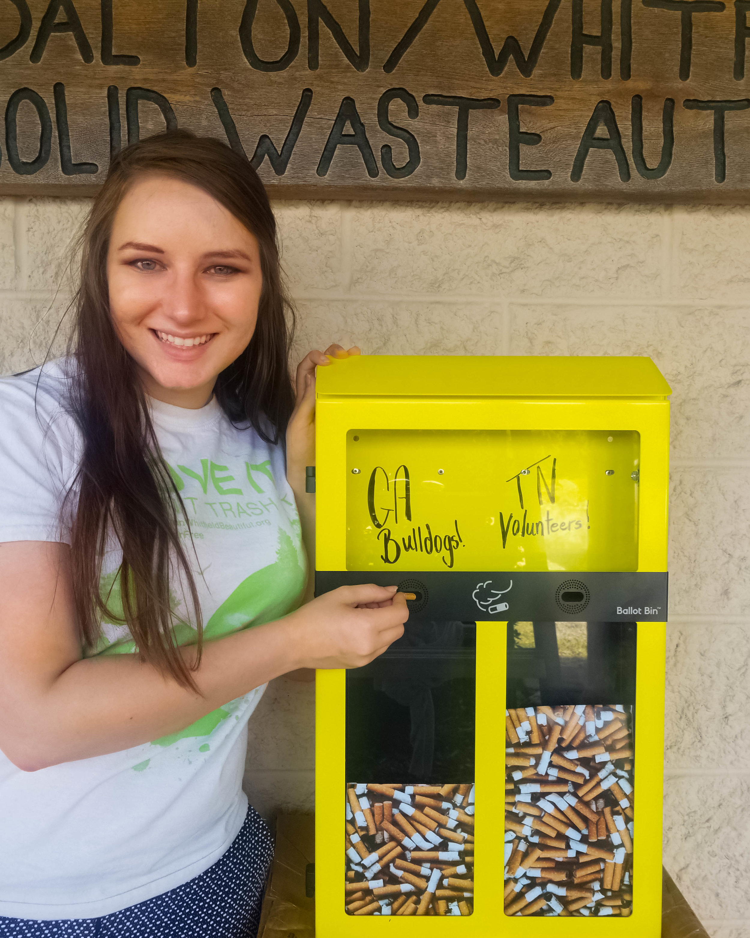 Executive Director, Amy Hartline, poses with one of the specially ordered Ballot Bins to demonstrate how people can vote for one of two options using cigarette litter.