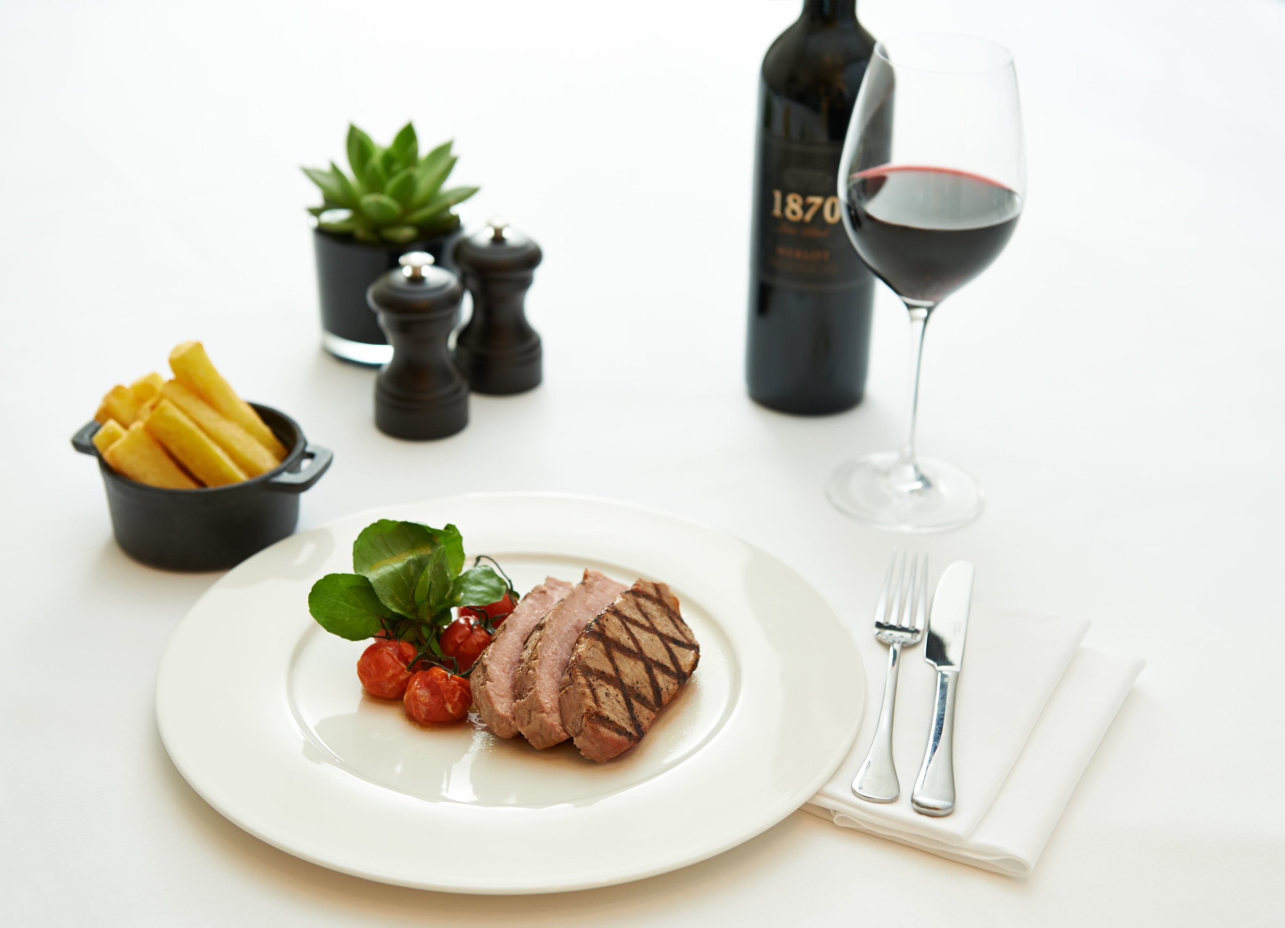 steak and a bottle of wine on a restaurant table