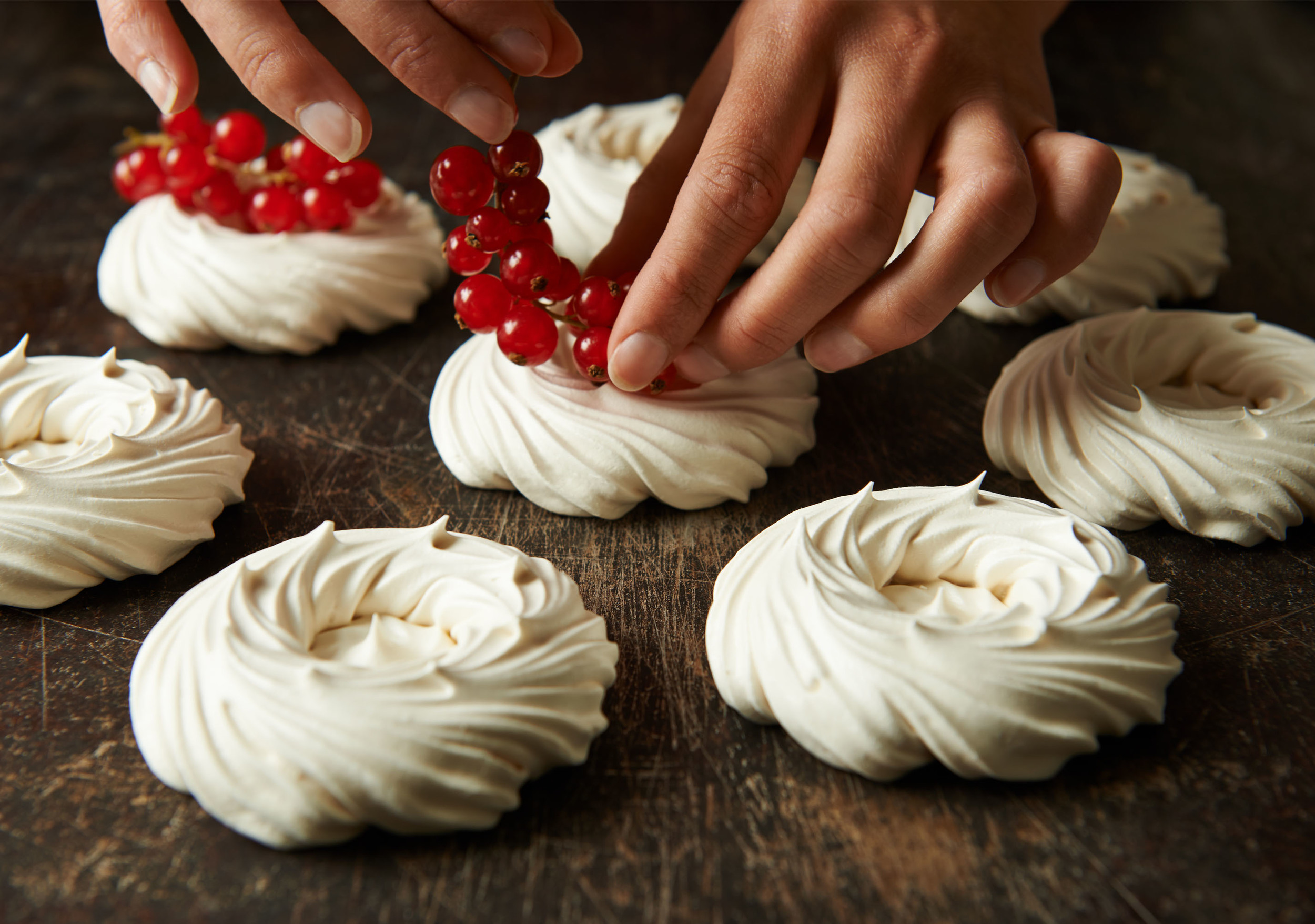 meringues being decorated with redcurrants