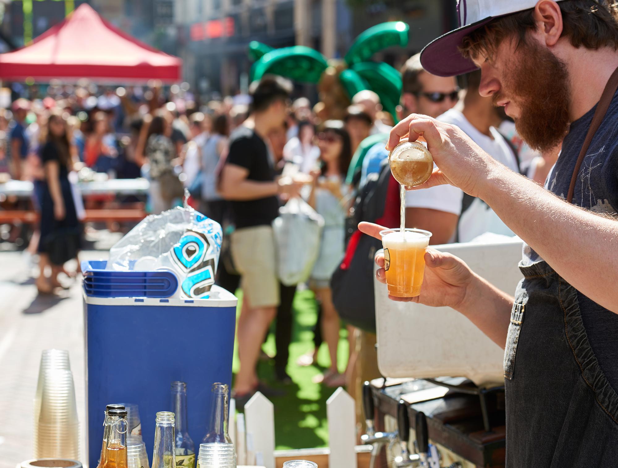 man serving beer at a street food market