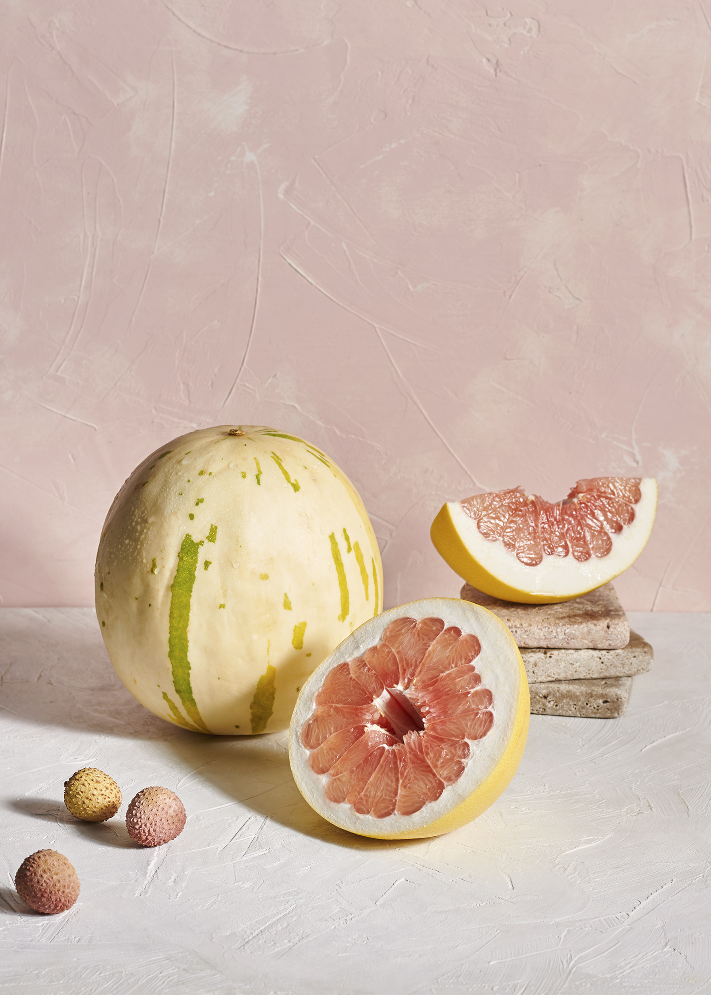 still life image of pomelo and lychees