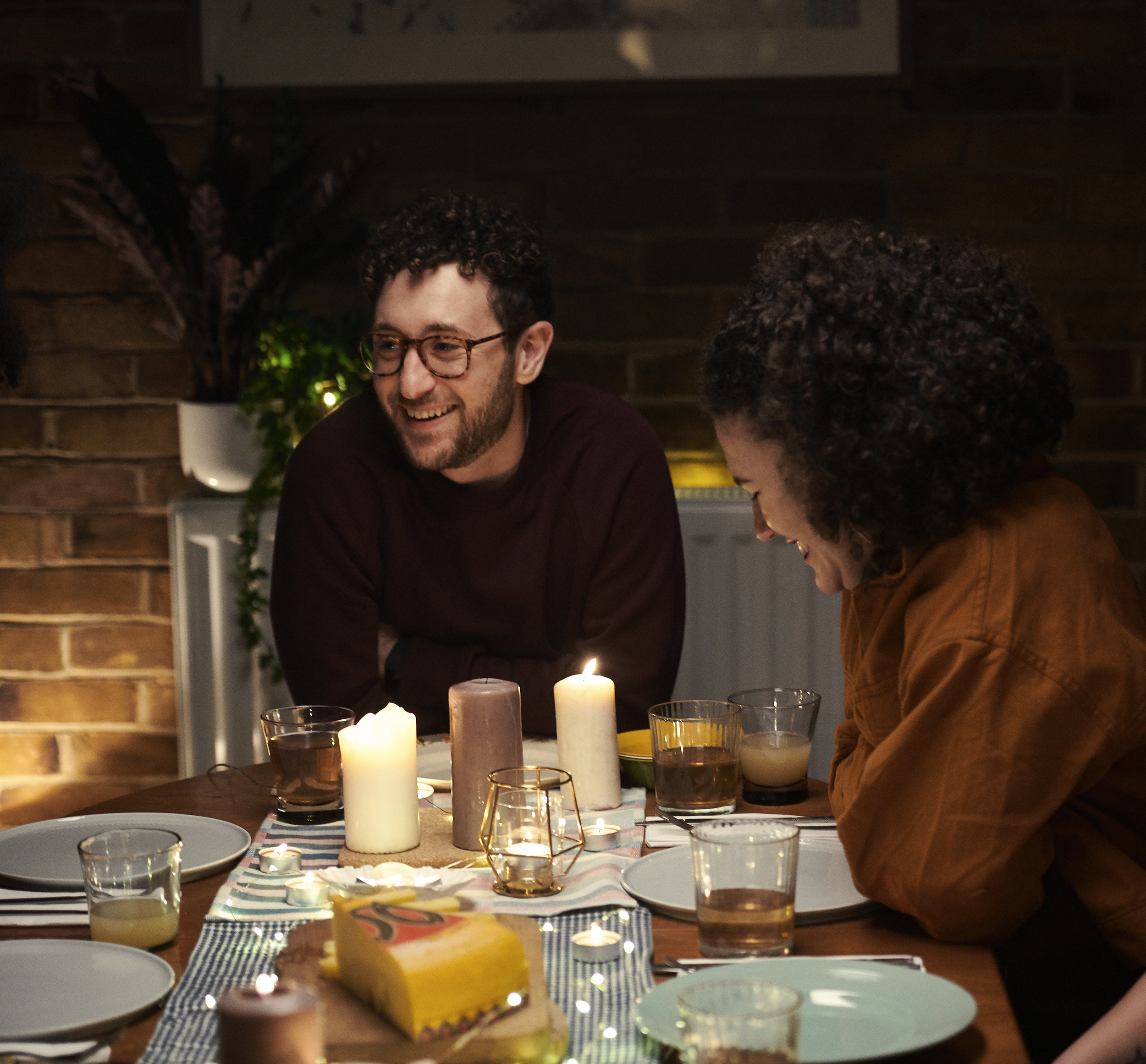 Lifestyle photography of a young couple at a dinner table with drinks