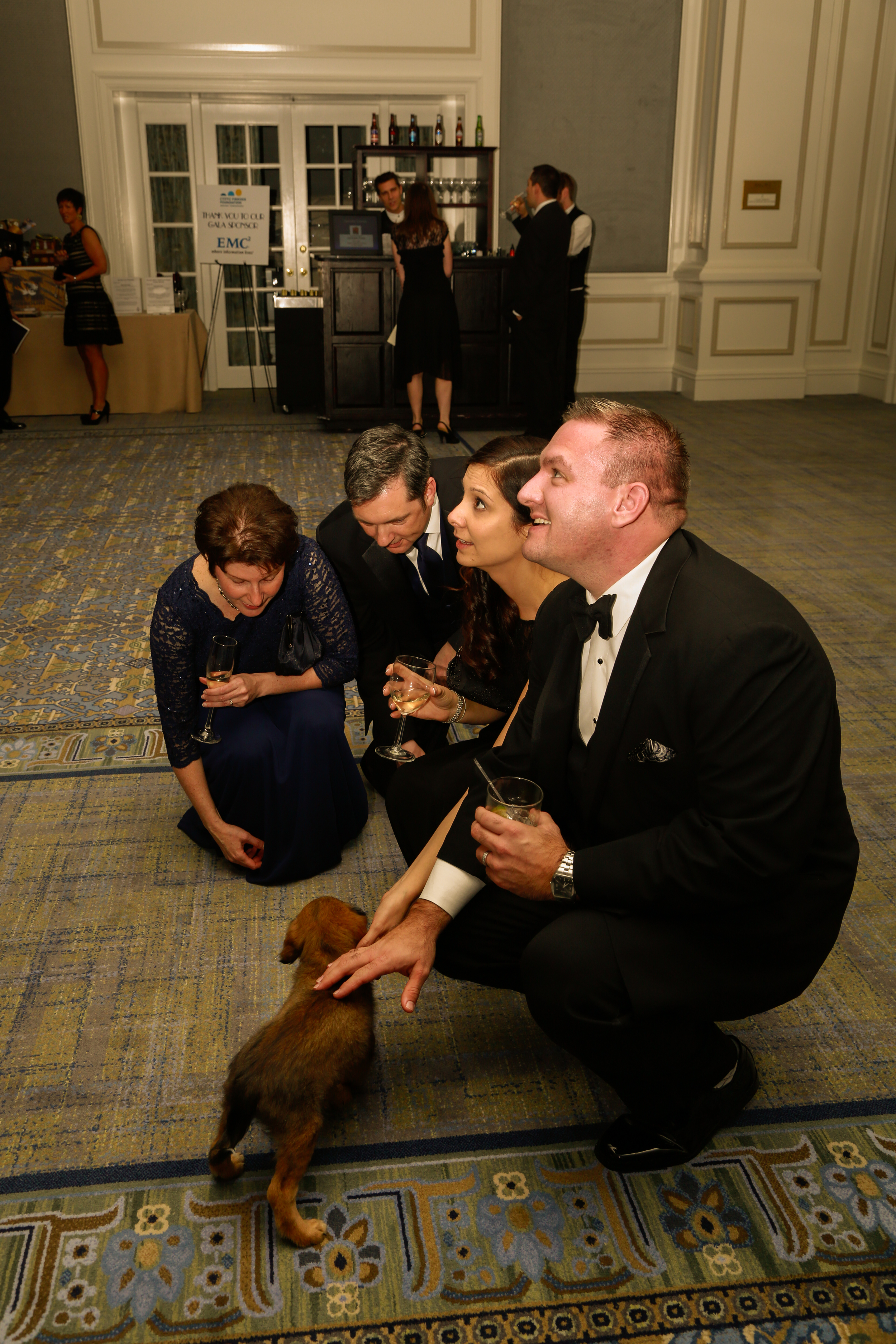 guests playing with the sweet puppy, one of the featured live auction items.
