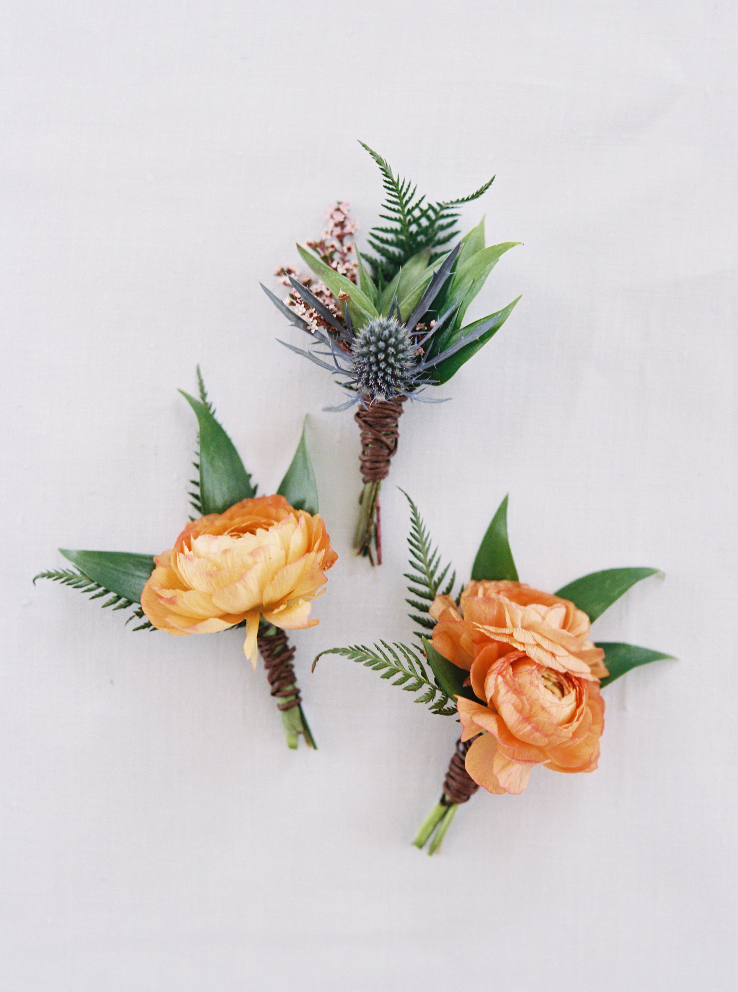 Flowers by Lace and Lilies, blue thistle, peach and orange ranunculus, fern and bay leaf boutonnieres - summer mountain wedding - texture for groom