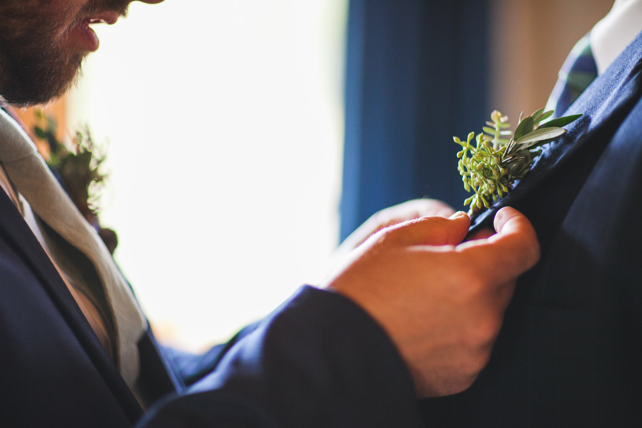 Flowers by Lace and Lilies, pinning on a boutonniere, mountain rustic wedding - groom and groomsman