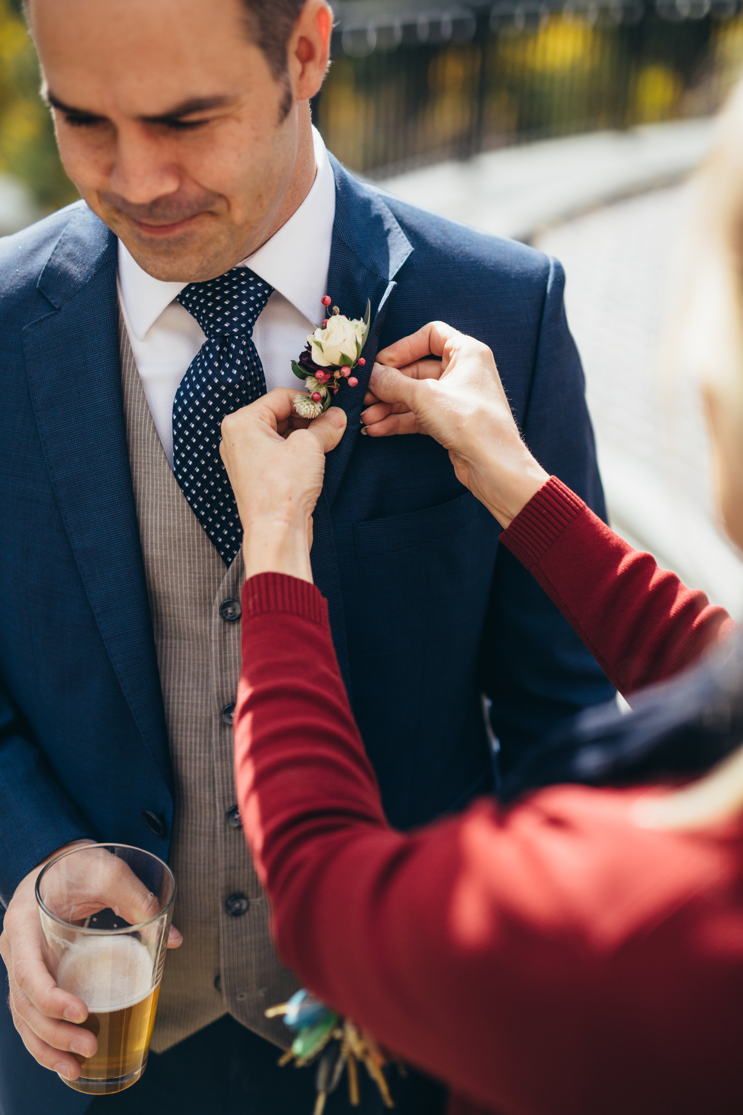Flowers by Lace and Lilies, pinning on a boutonniere with a beer! Blue three piece suit with white spray rose and berry boutonniere
