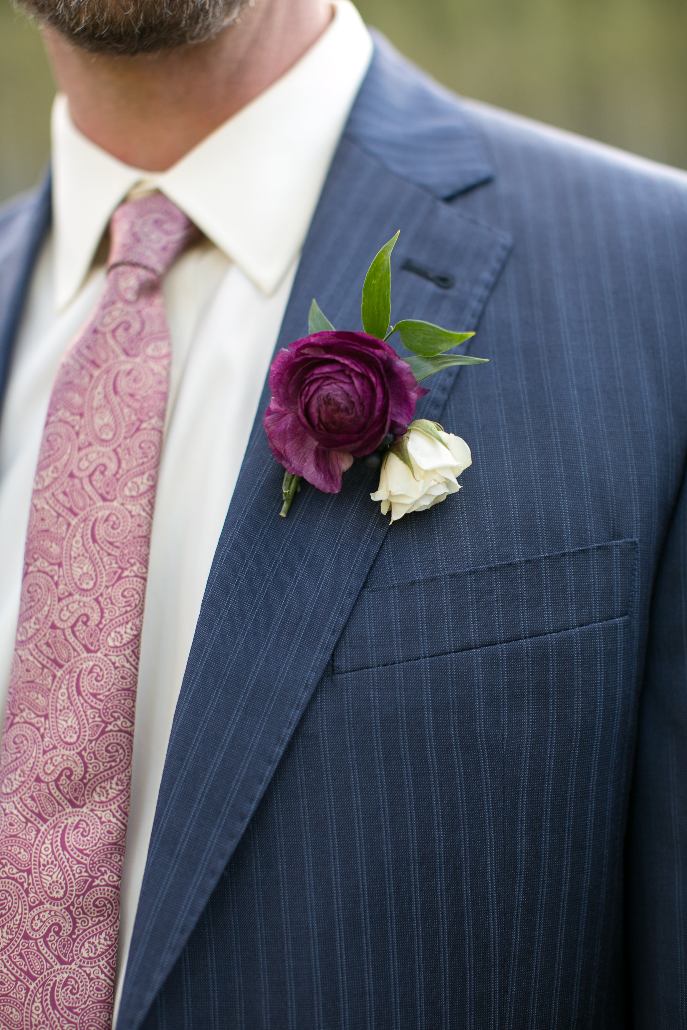 Flowers by Lace and Lilies, groom in blue suit, purple ranunculus, spray rose and italian ruscus boutonniere