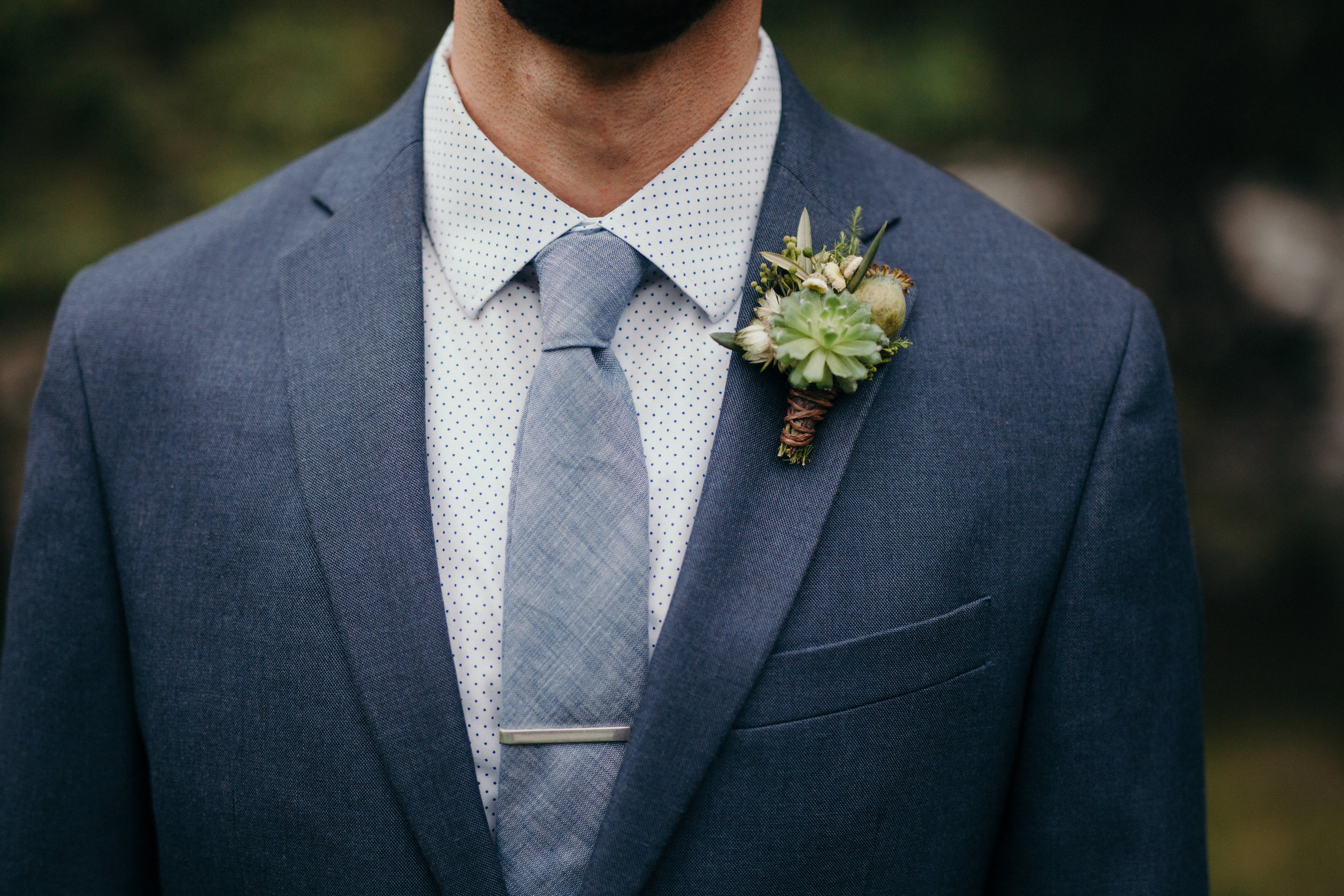 Flowers by Lace and Lilies succulent, poppy pod mountain boutonniere - groom in blue suit