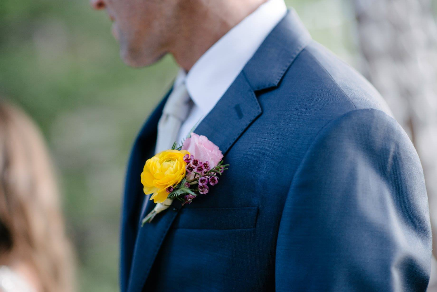 Flowers by Lace and Lilies, Blue suit groom, yellow, pink and purple boutonniere - ranunculus and wax flower.