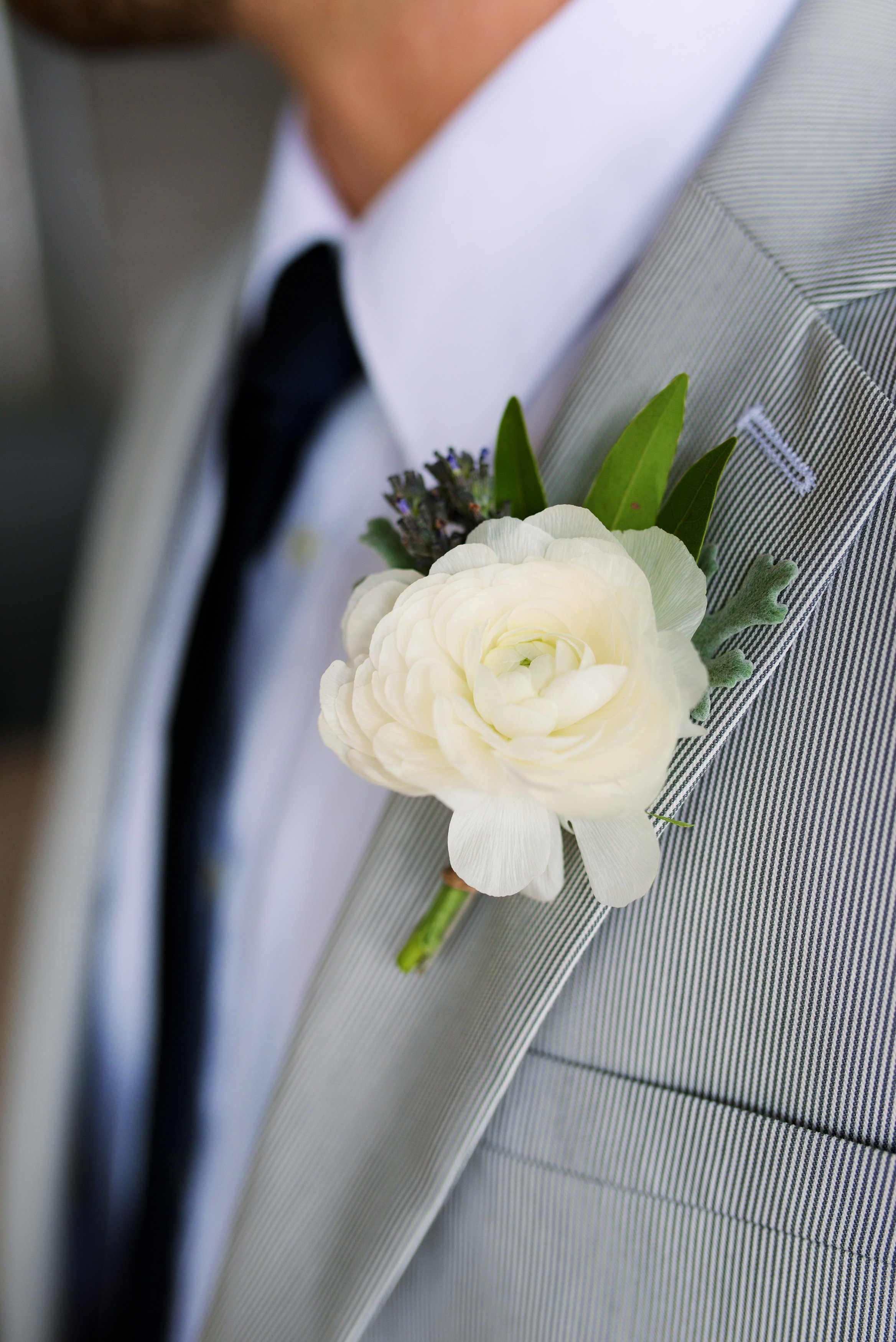Flowers by Lace and Lilies, White ranunculus boutonniere with lavender and dusty miller - groom in gray suit