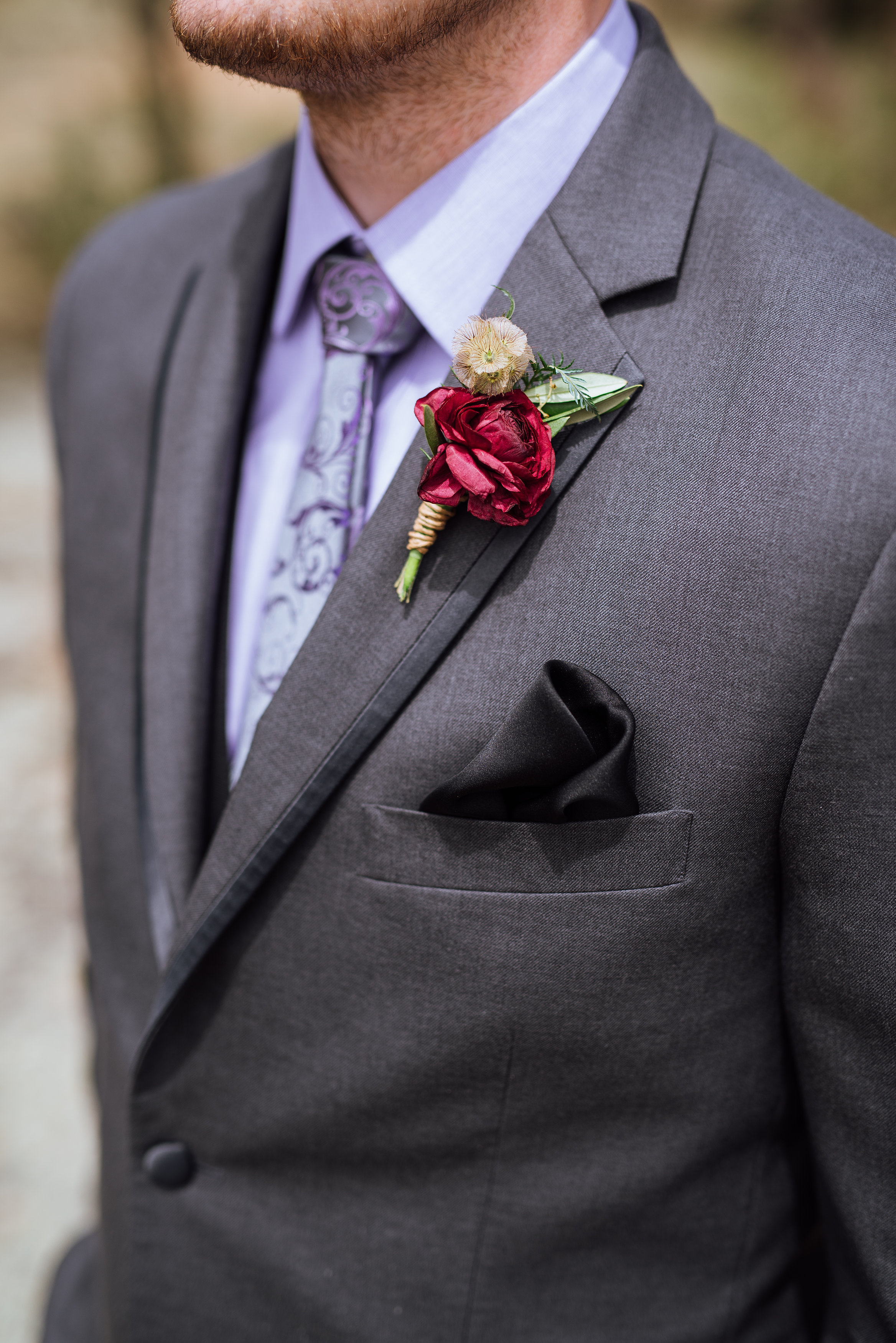 Flowers by Lace and Lilies, burgundy ranunculus, olive branch, and scabiosa pod boutonniere