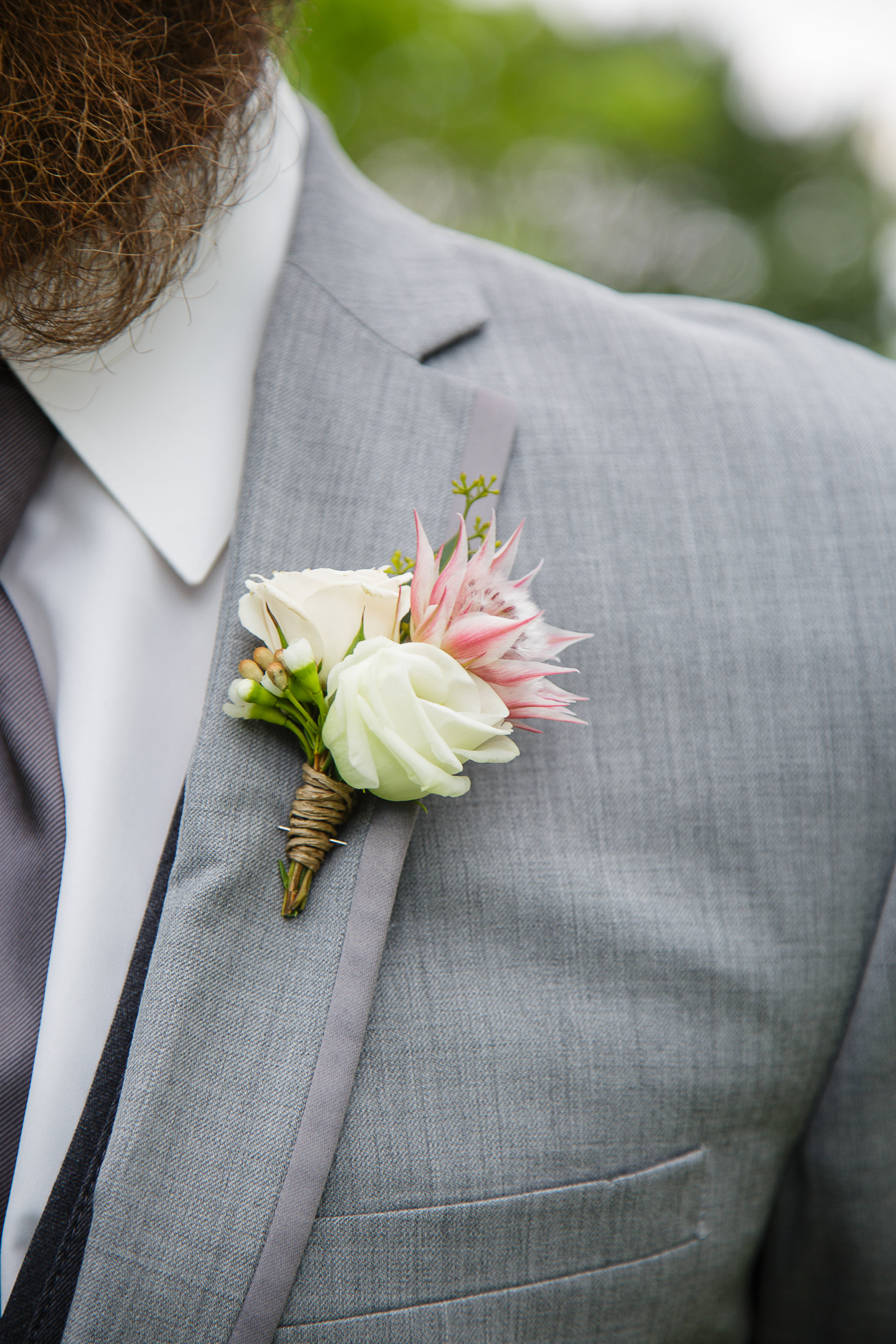 Flowers by Lace and Lilies, White and Blush boutonniere, spray rose and blushing bride - grooms grey suit - summer wedding