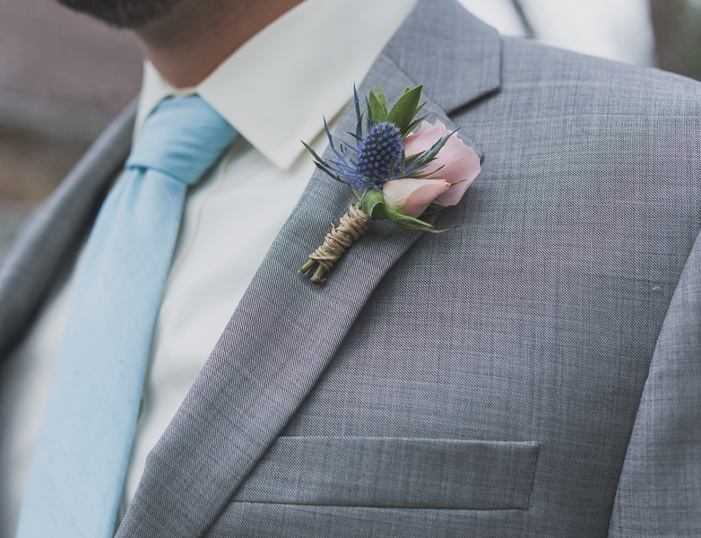 Flowers by Lace and Lilies, blue thistle and blush spray rose boutonniere, grey suit groom