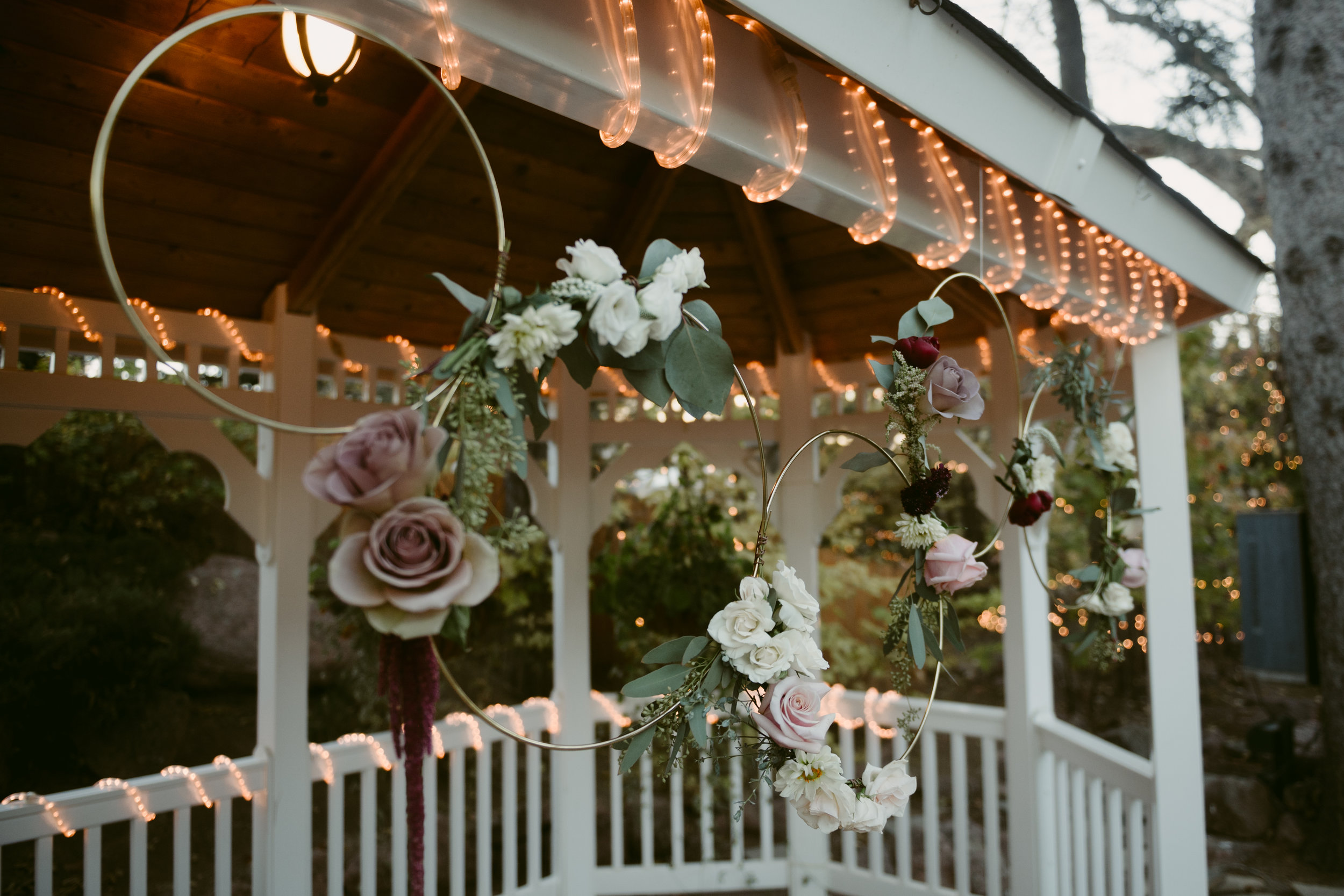 Flowers by Lace and Lilies, ceremony flowers, tapestry house wedding, circle flowers, hoop flowers, foliage, greenery, lavender flowers, roses, arch flowers, colorful bloom, pink wedding flowers, cross flowers, garland, pergola flowers,  ceremony decor