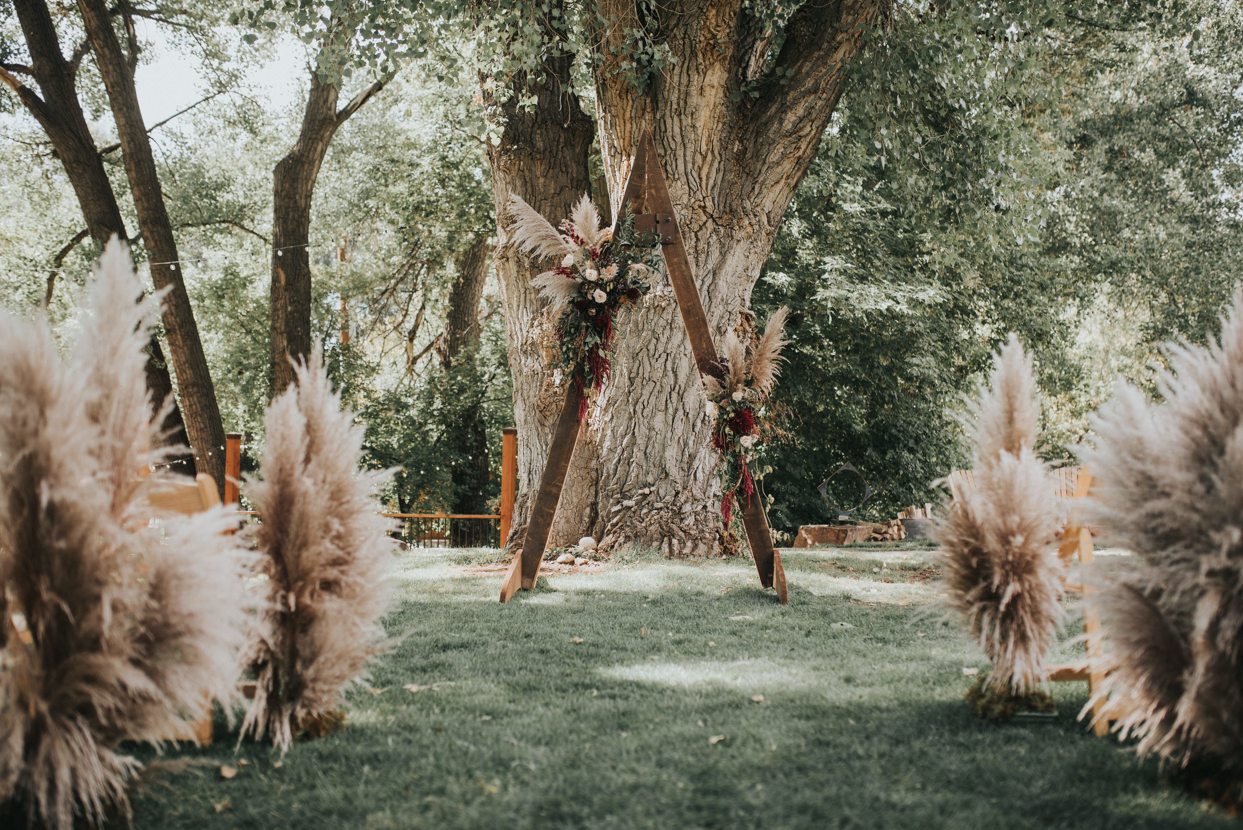 Flowers by Lace and Lilies, boutonniere, wedding flowers, jewel tones, pampas grass, hops, texture, colorado wedding, a-frame arch, arch flowers, altar flowers, ceremony flowers, moody toned wedding, pampas grass, aisle flowers