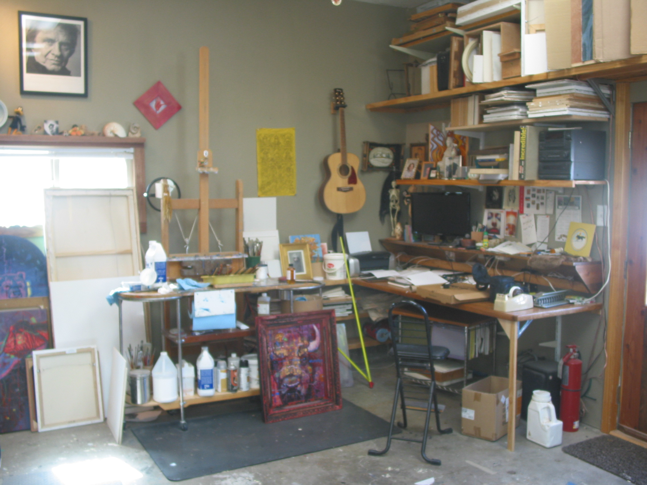 Here is a view of my easel without a painting on it. My Painting Table that holds my pallet and on the right a table and a computer screen that I view my photos and references with. You can see the guitar on the wall and a poster of the Man in Black. There are unfinished canvases on the floor to the left.
