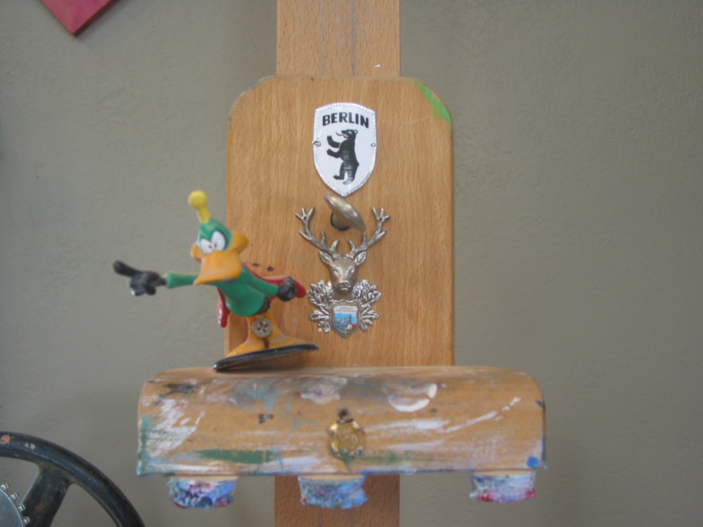 "The top jaw of my easel is adorned with Daffy as ""Stupor Duck"" The Berlin Bear shield I got in Berlin visiting Jake and the Garmisch-Partenkirchen  Shield I got when we all went to visit Hilary."