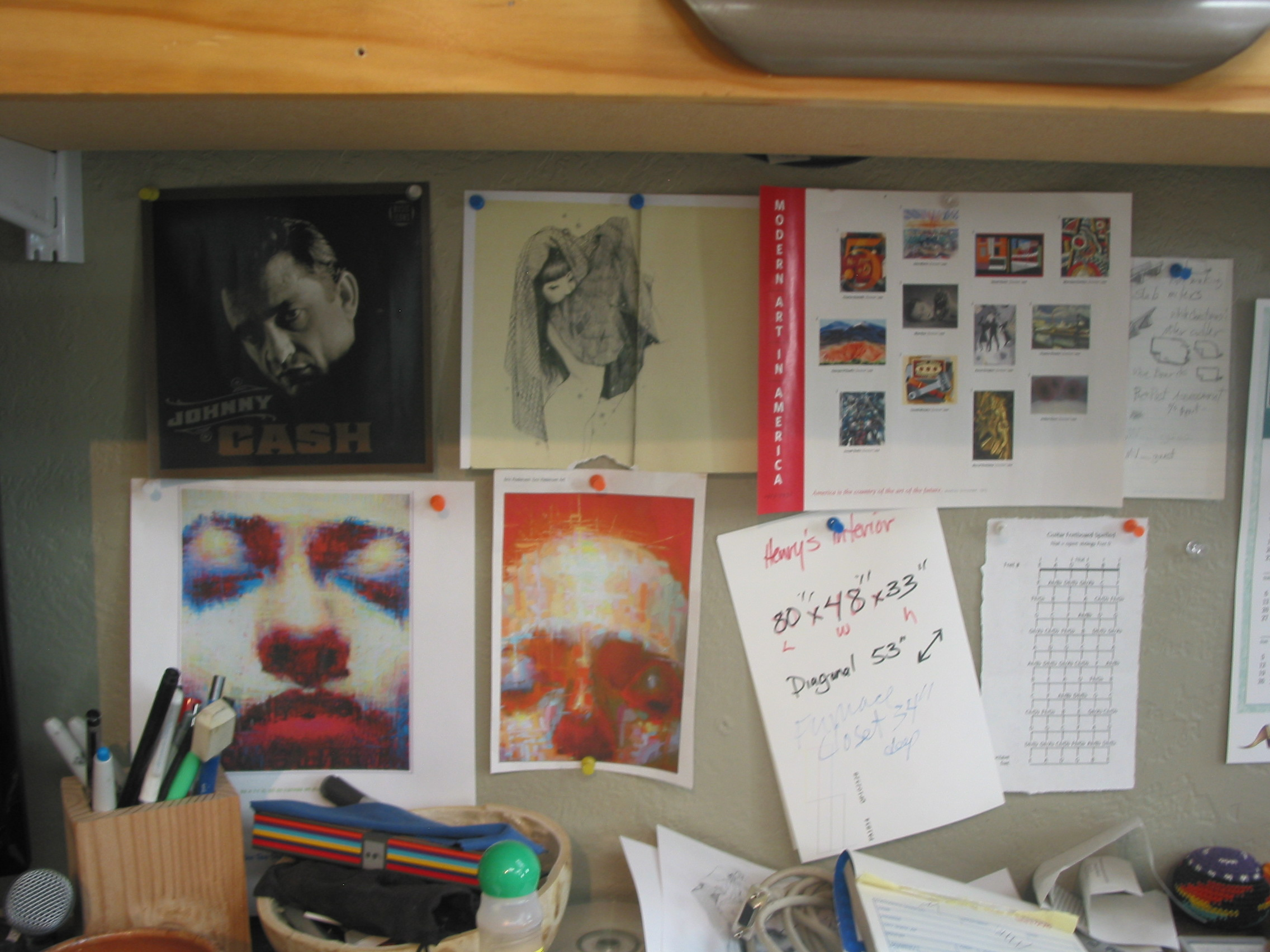 Some picts above my desk. There is a picture of Johnny Cash, two images by Eric Pederson, a stamp set of American Modern Art, notes and a fret chart.