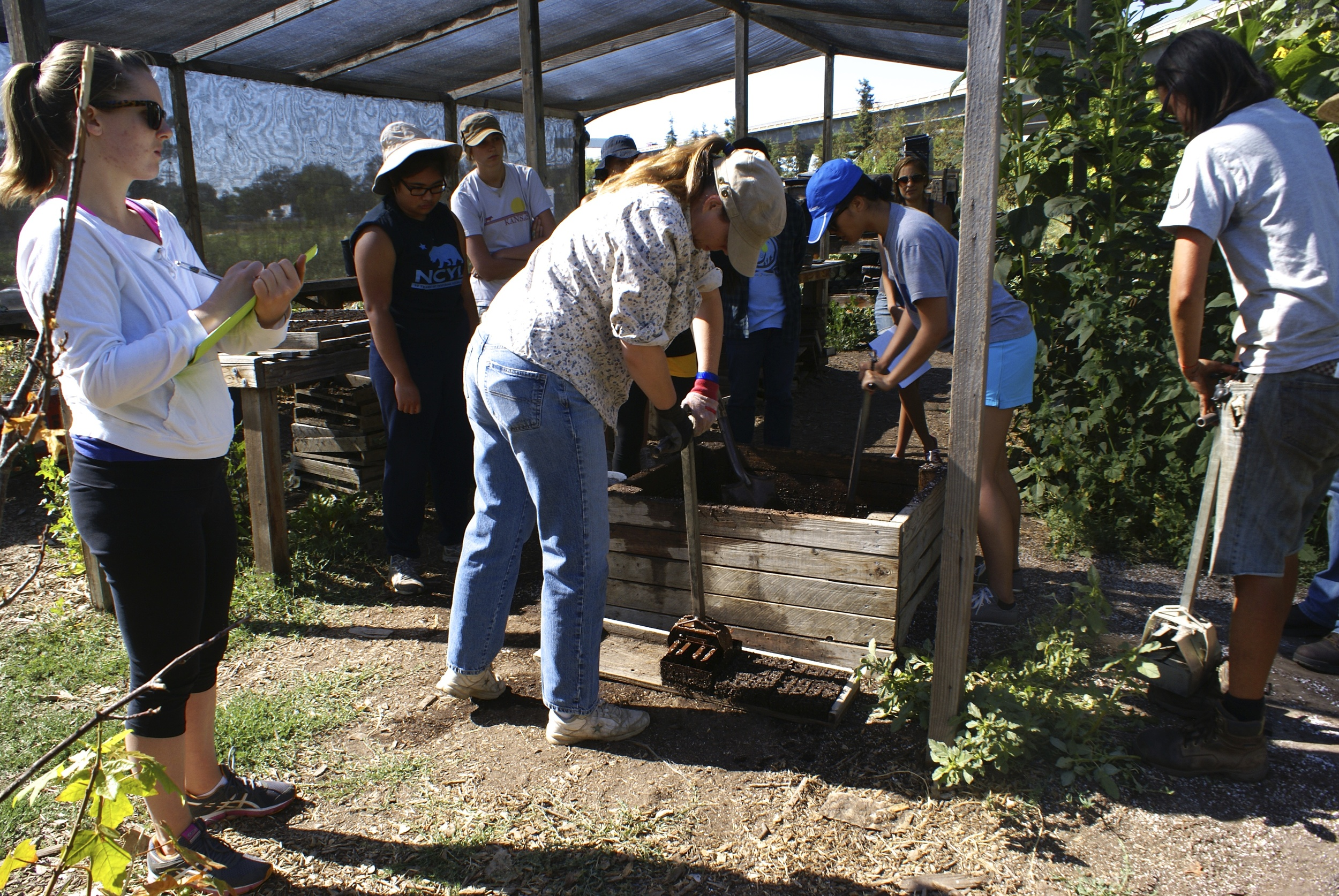 Greenhouse training includes soil mixing and soil block formation for seeding.