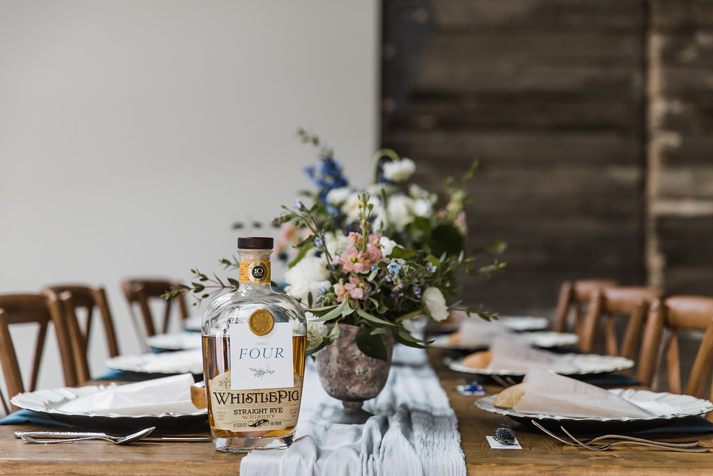 wedding tablescape with whiskey bottle table number and gold wax seal