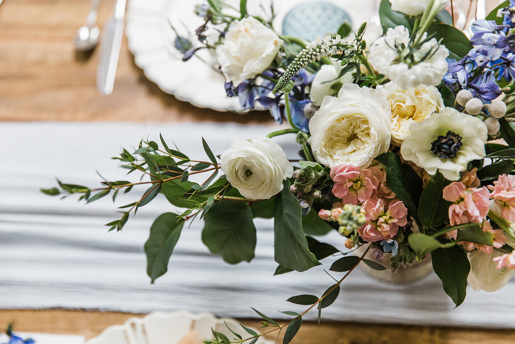 wedding floral centerpiece with soft whites and accents of blue