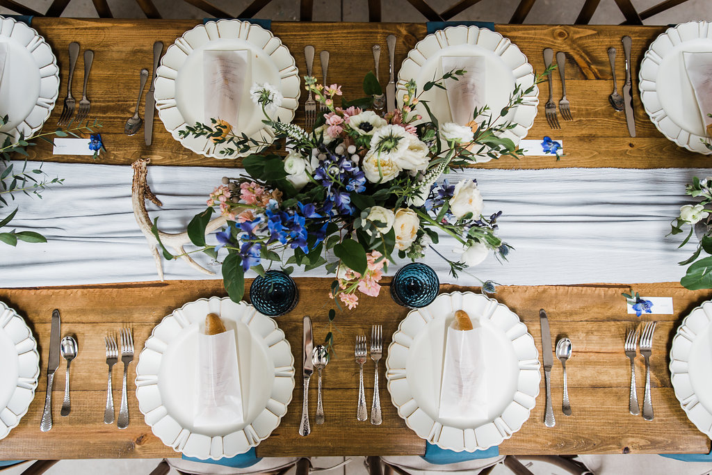bluestem hall wedding dinner tablescape with antique chargers and blue accented florals