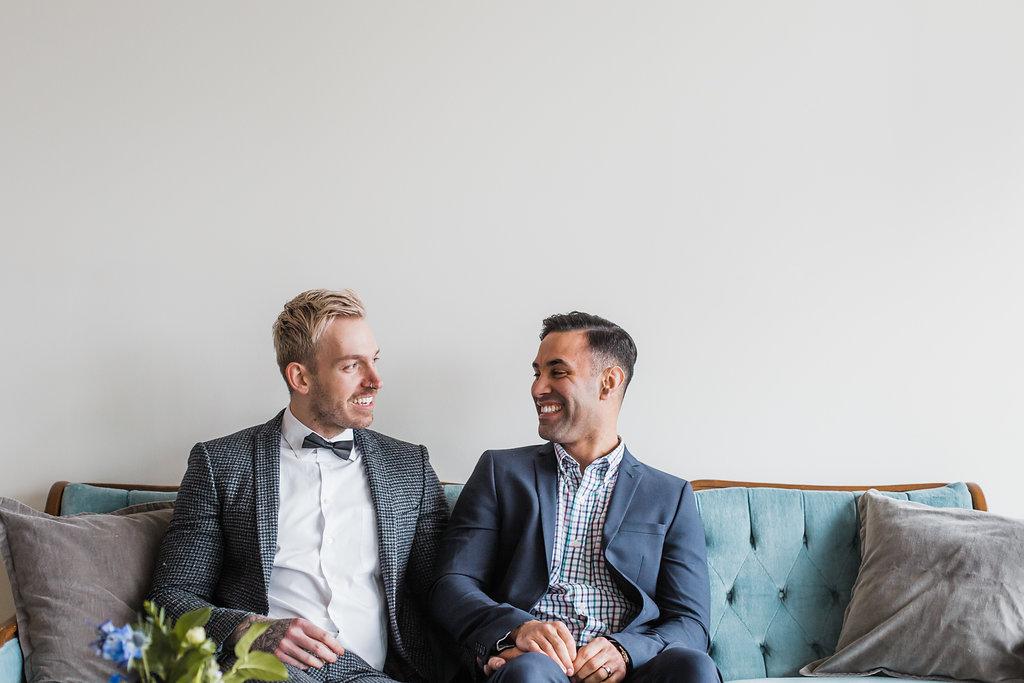 same sex wedding couple posing on vintage sofa