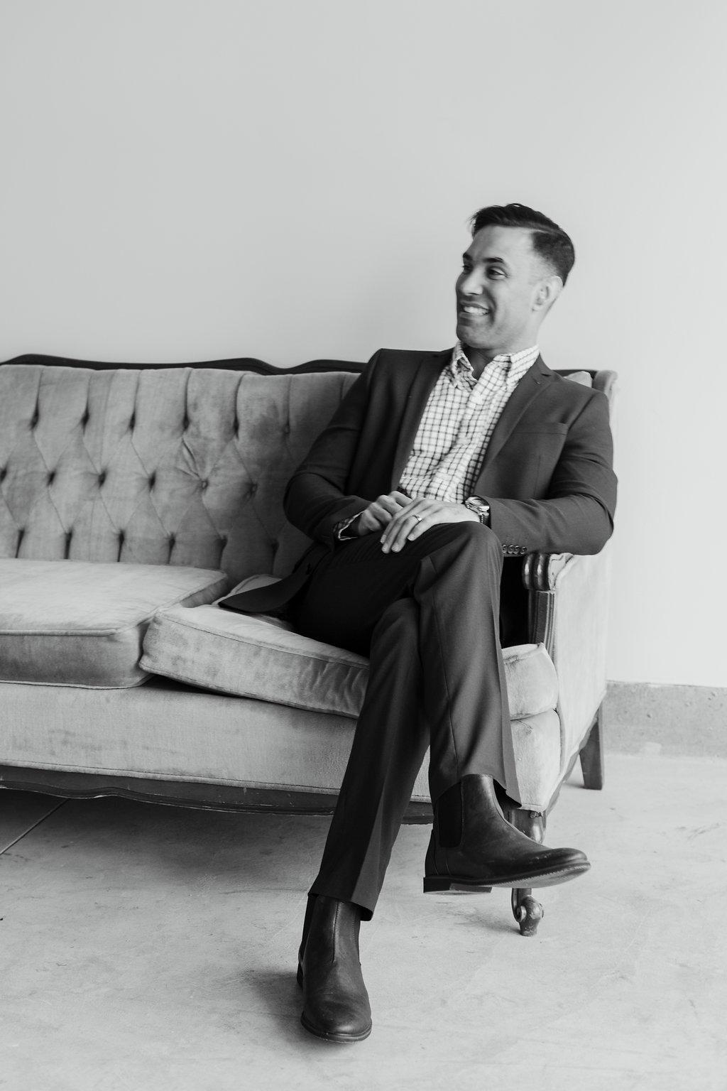 groom casually sitting on vintage sofa for wedding portrait