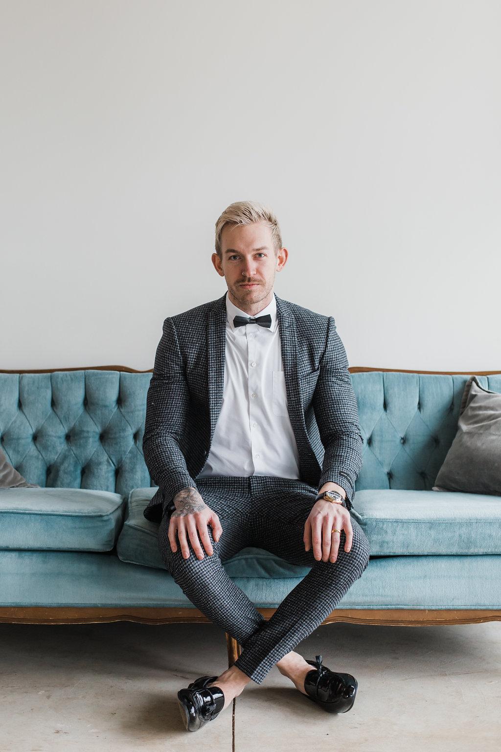 groom sitting on vintage sofa for wedding portrait