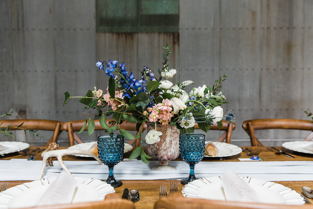 blue accented wedding tablescape with antlers and vintage plates