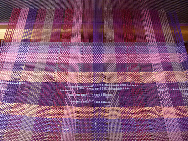 The warp on the loom with the colors starting to come together and the Sakiori strips adding some magic.