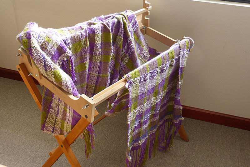 This is the rigid heddle loom that allowed me to start weaving again while waiting for my loom to arrive. Draped on it is the Wedding Shawl I wove with this loom.