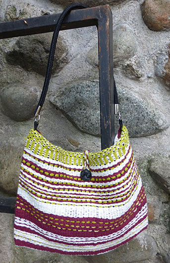 I love the contrast between the burgundy and lime green in this bag. The commercial strap is a black woven style. This bag is lined in black with one side pocket. The closure is a twisted cord and black button.